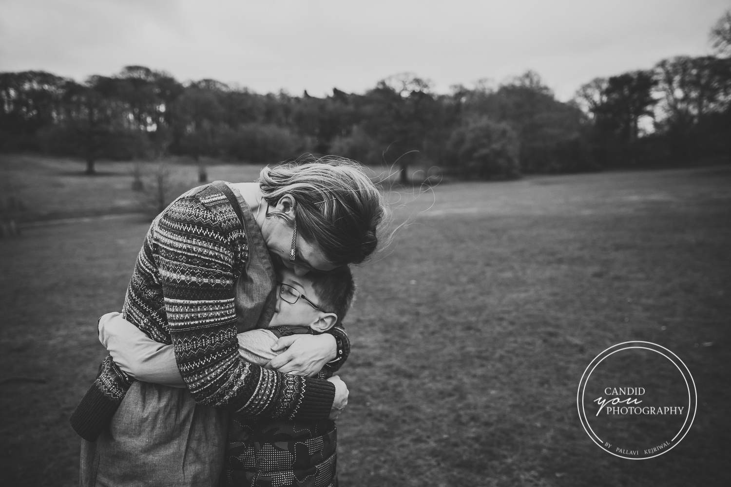 Harborne mum bends down to hug son black and white photography