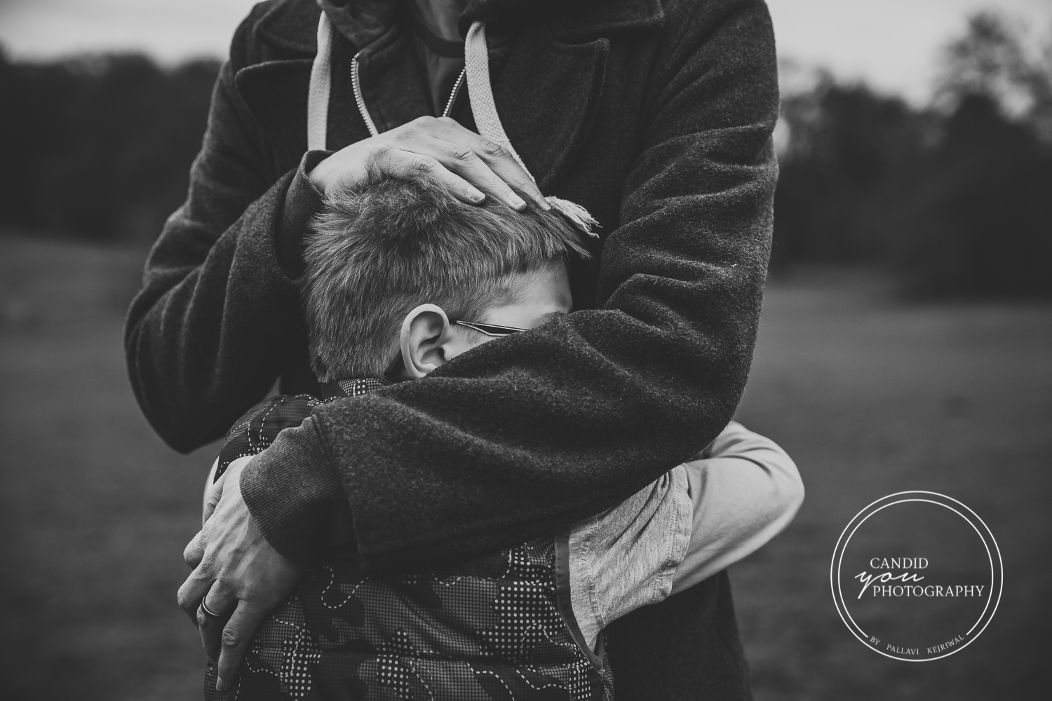 Dad hugs son with love and son nestles head in dad's body black and white photography