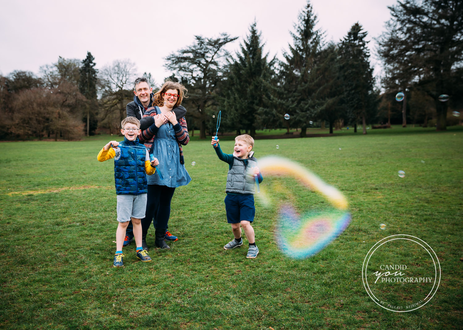 Harborne Family with two boys joyously blowing bubbles in park