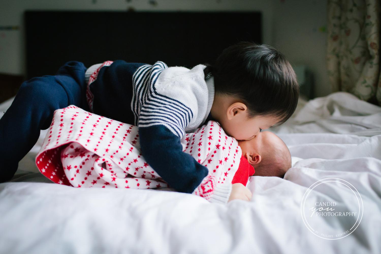 Birmingham UK Asian brother kisses newborn baby sister sweetly