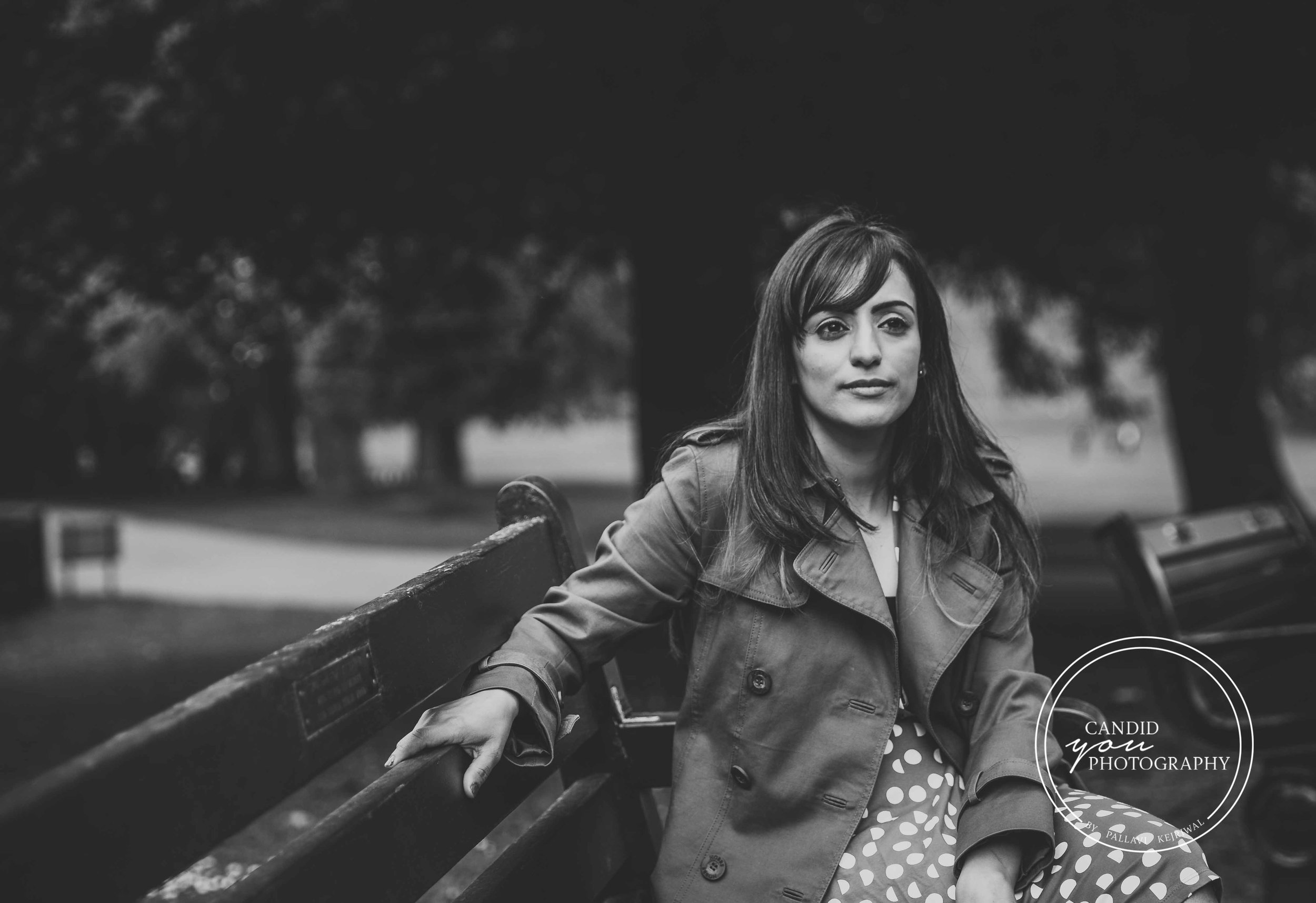 Beautiful lady sitting on park bench in burberry jacket