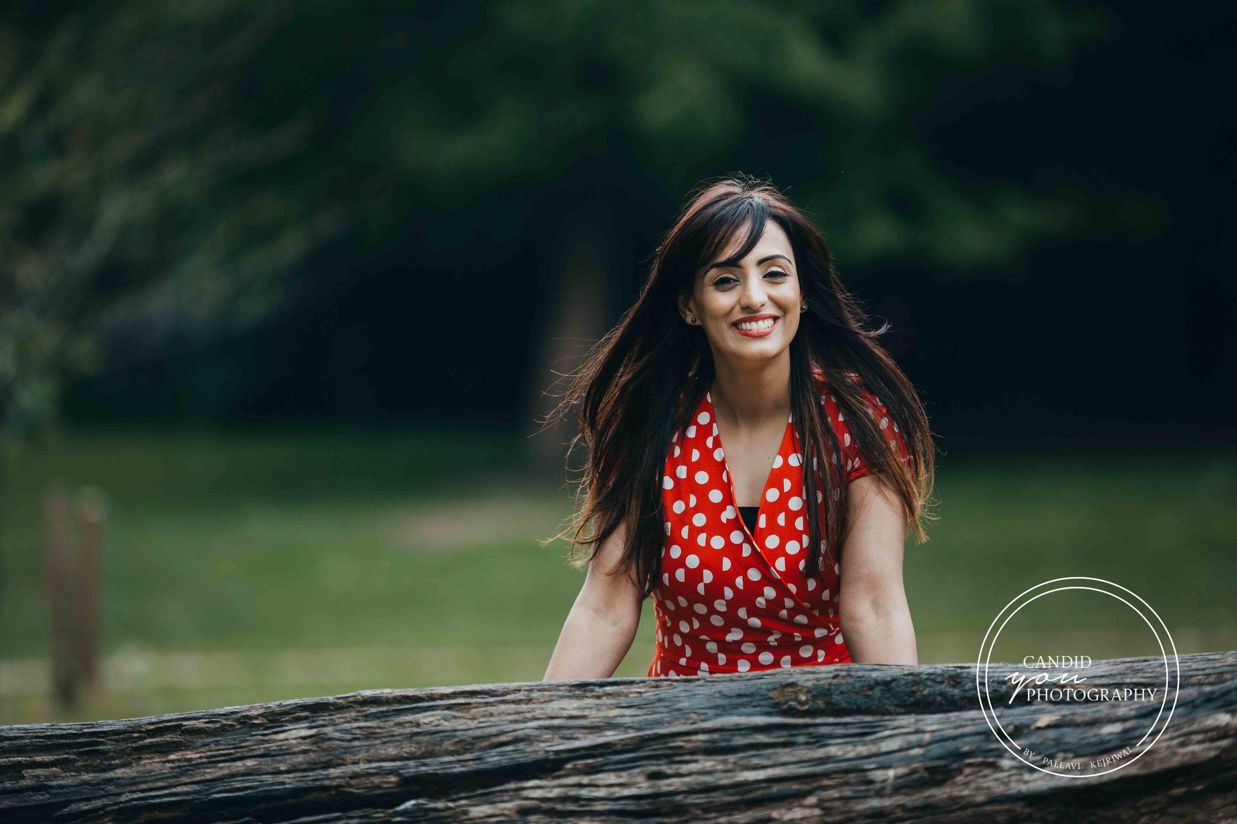 Beautiful lady smiling in orange polka dot dress in park
