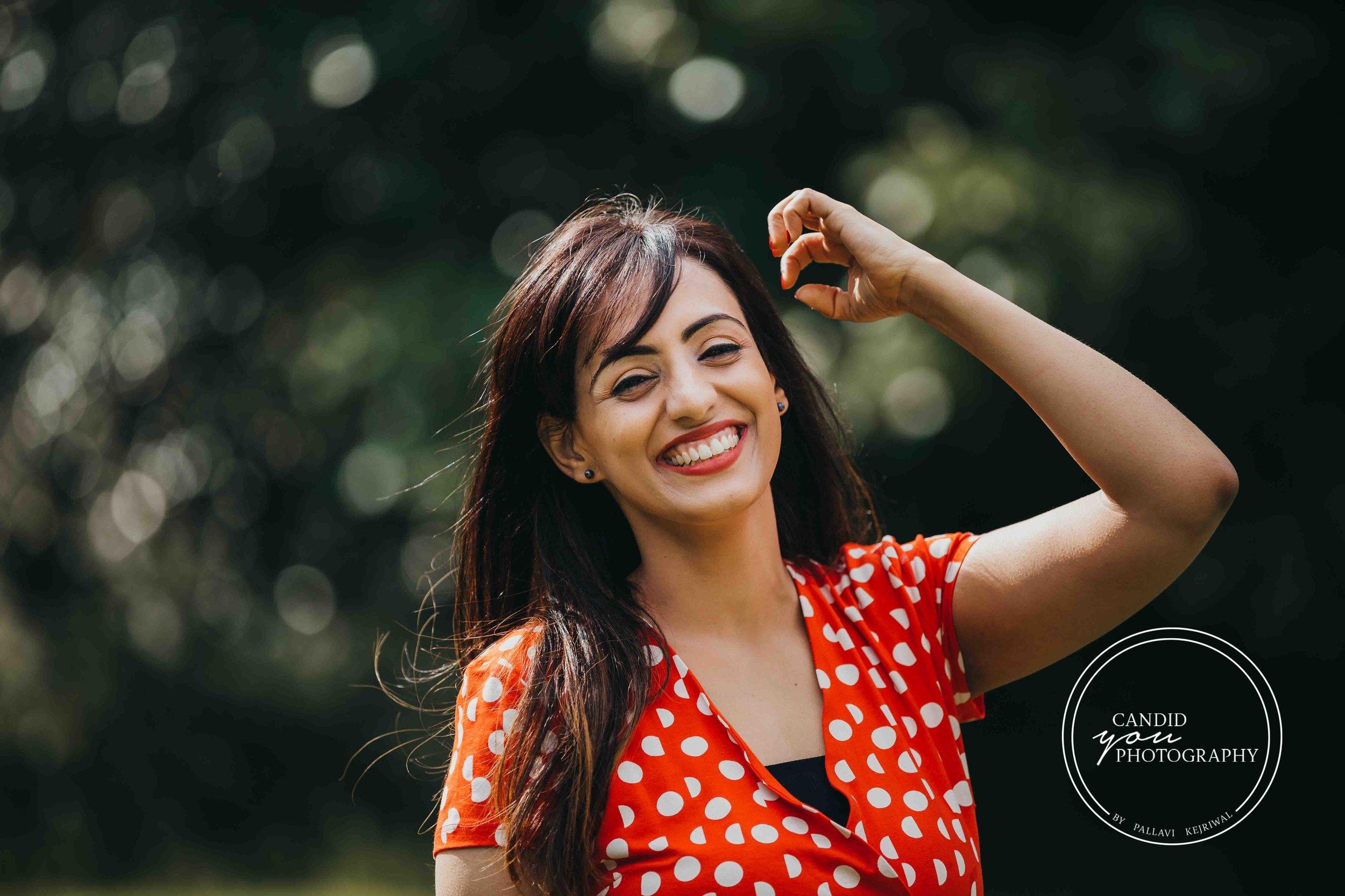 beautiful lady in orange polka dot dress flinging hair and smiling