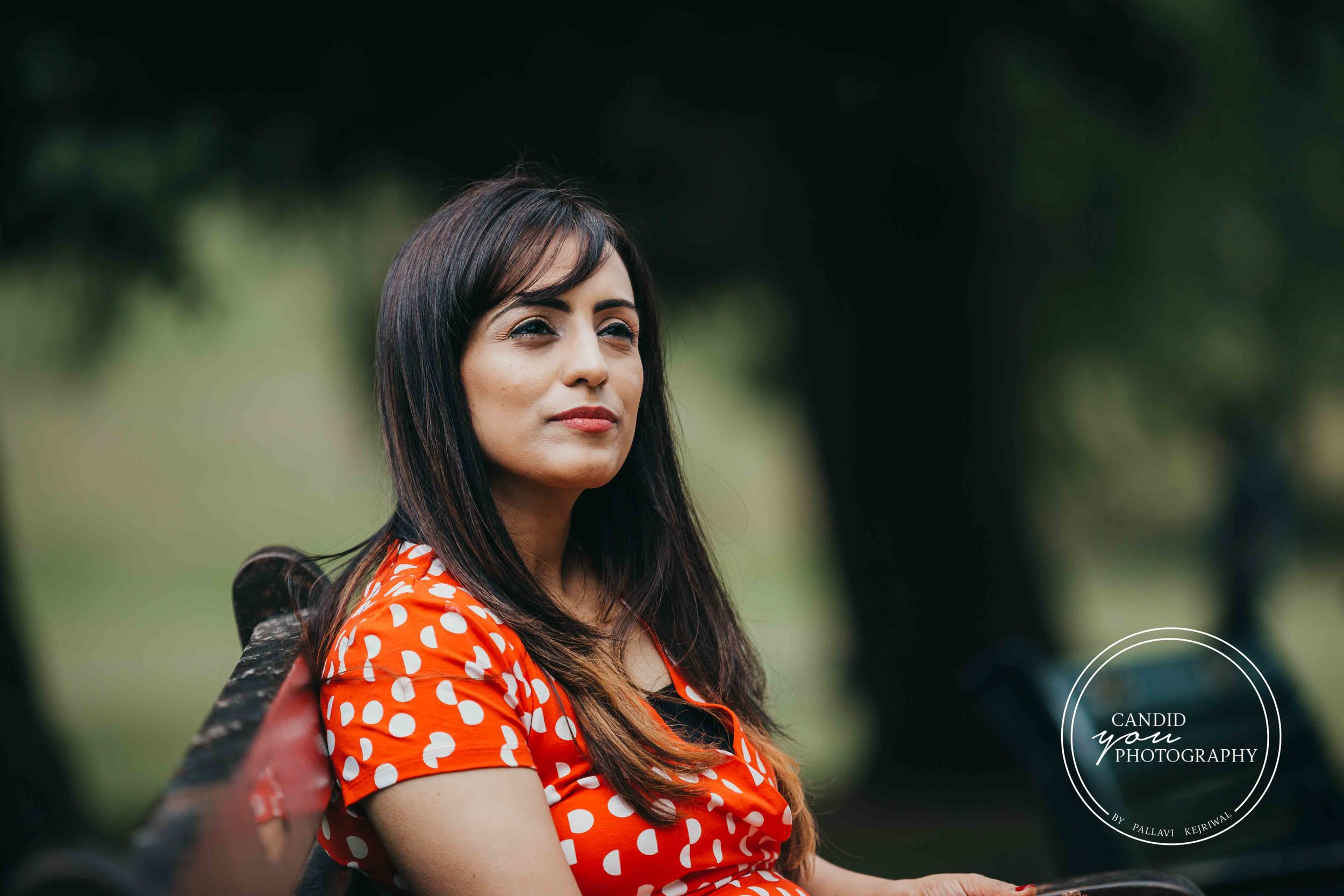 Beautiful lady sitting on park bench in orange polka dot dress