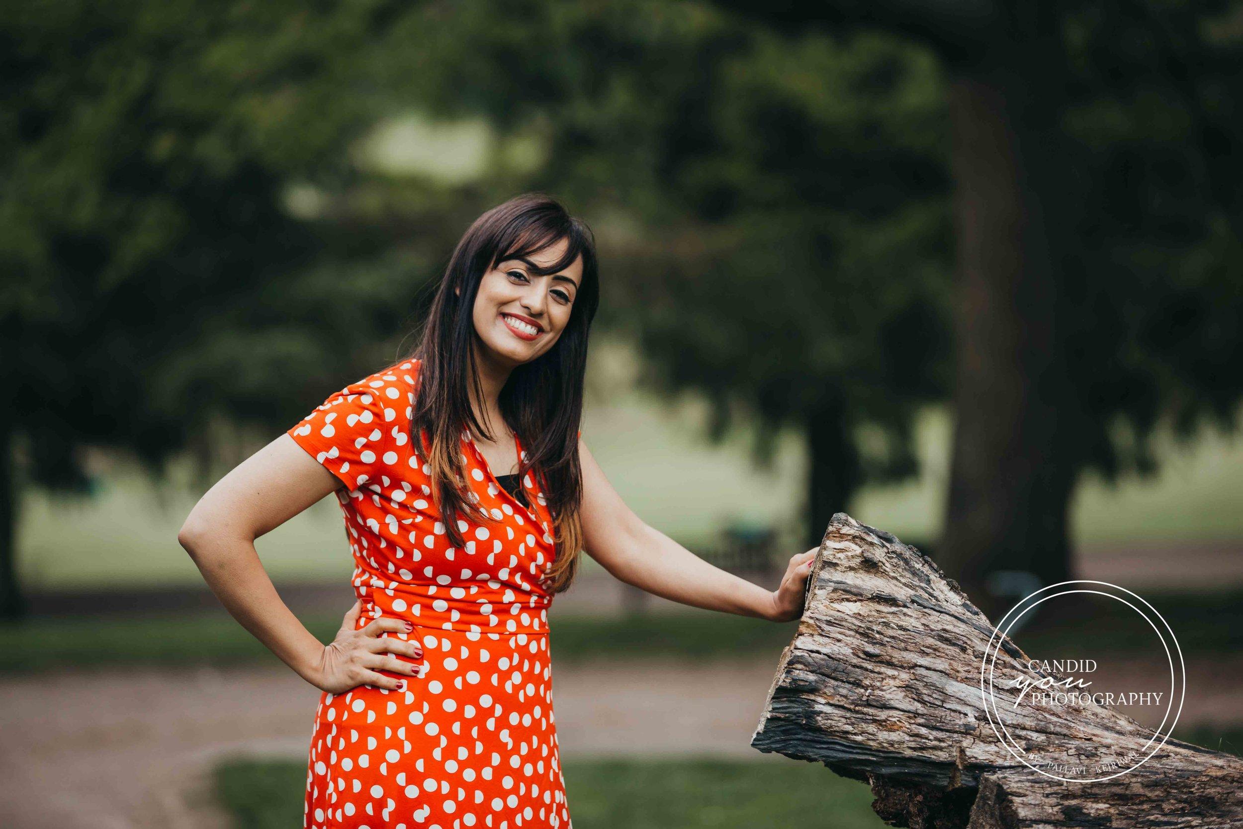 Beautiful woman in orange polka dot dress in park