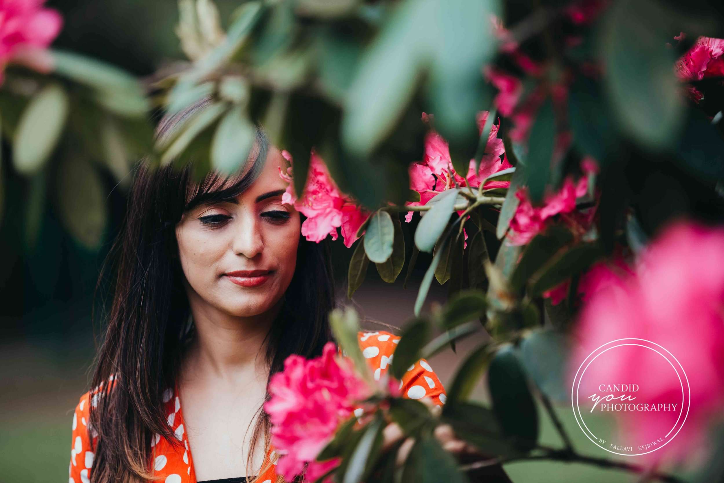 gorgeous woman looking at pink flowers
