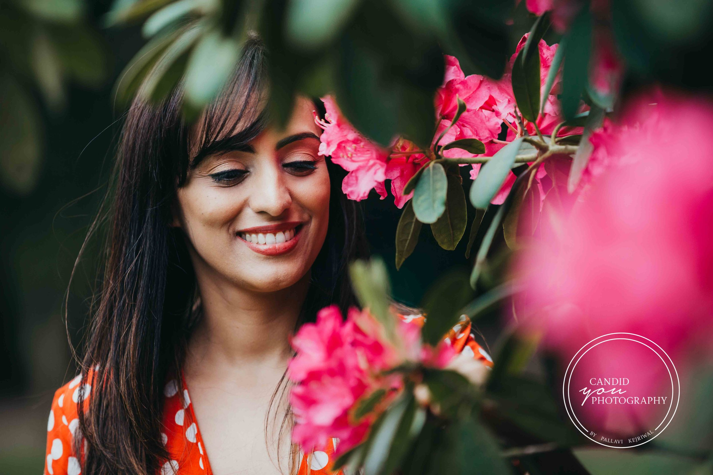 beautiful lady smiling at pink flowers