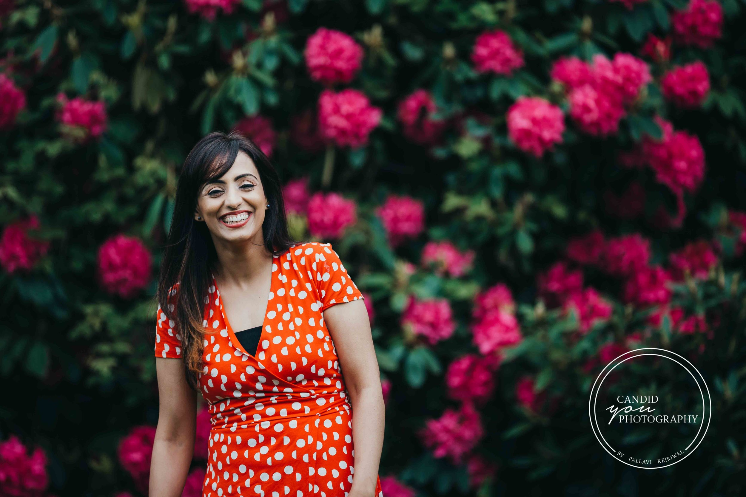 lady laughing in orange polka dot dress in front of pink flowers