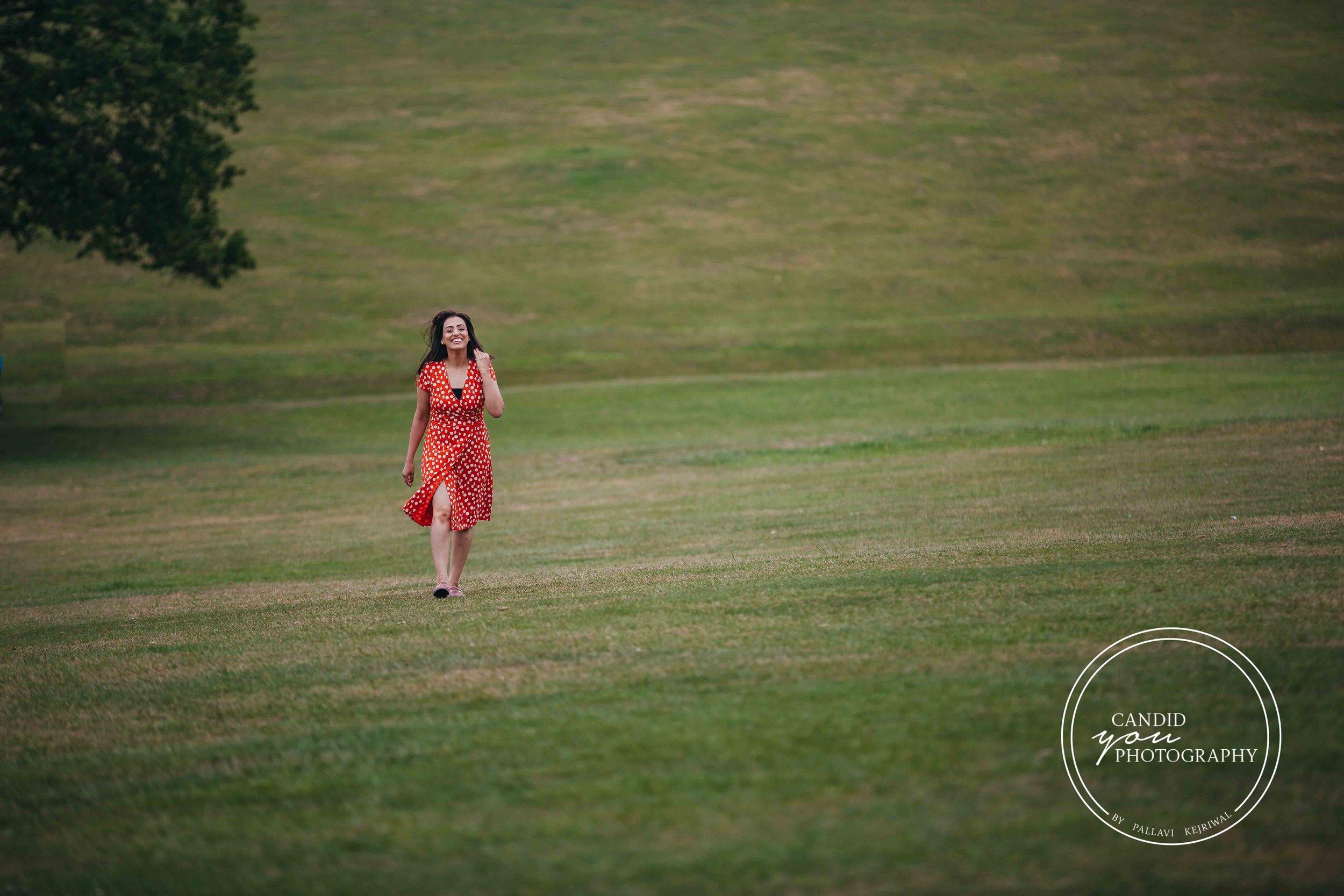 beautiful lady walking in park in orange polka dot dress