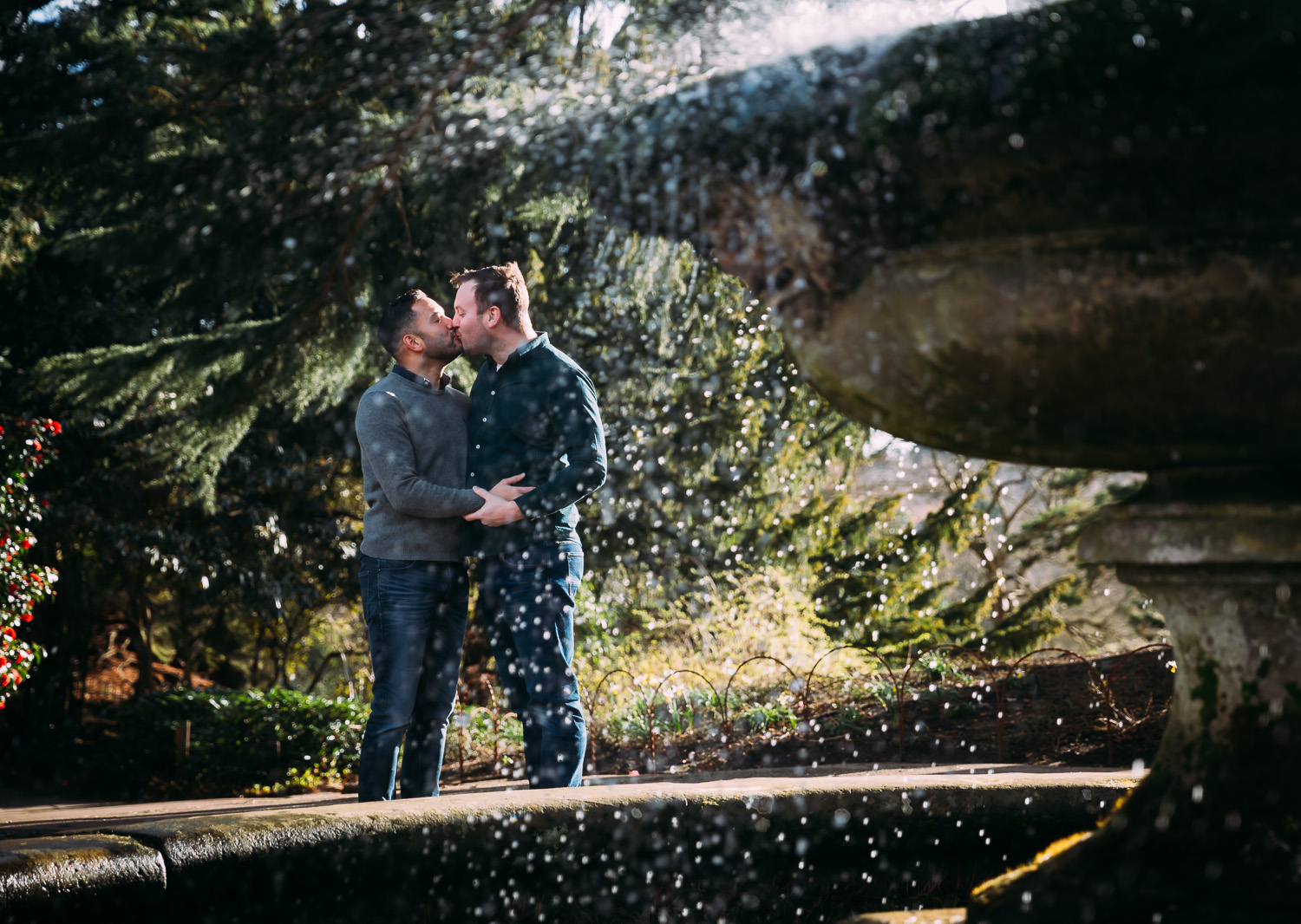 LGBTQ couple kissing near fountain in botanical gardens
