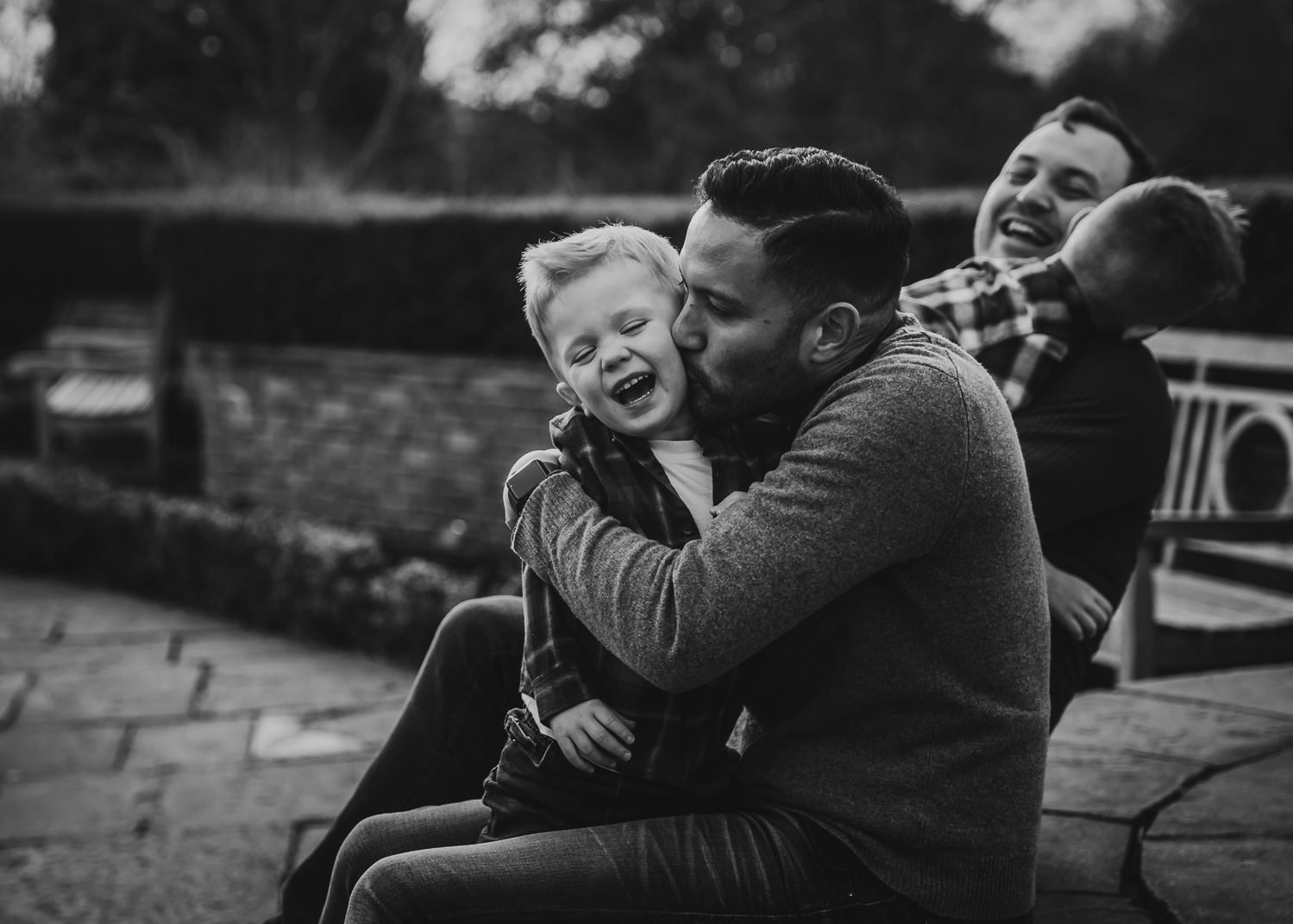 LGBTQ father deeply hugging adopted son