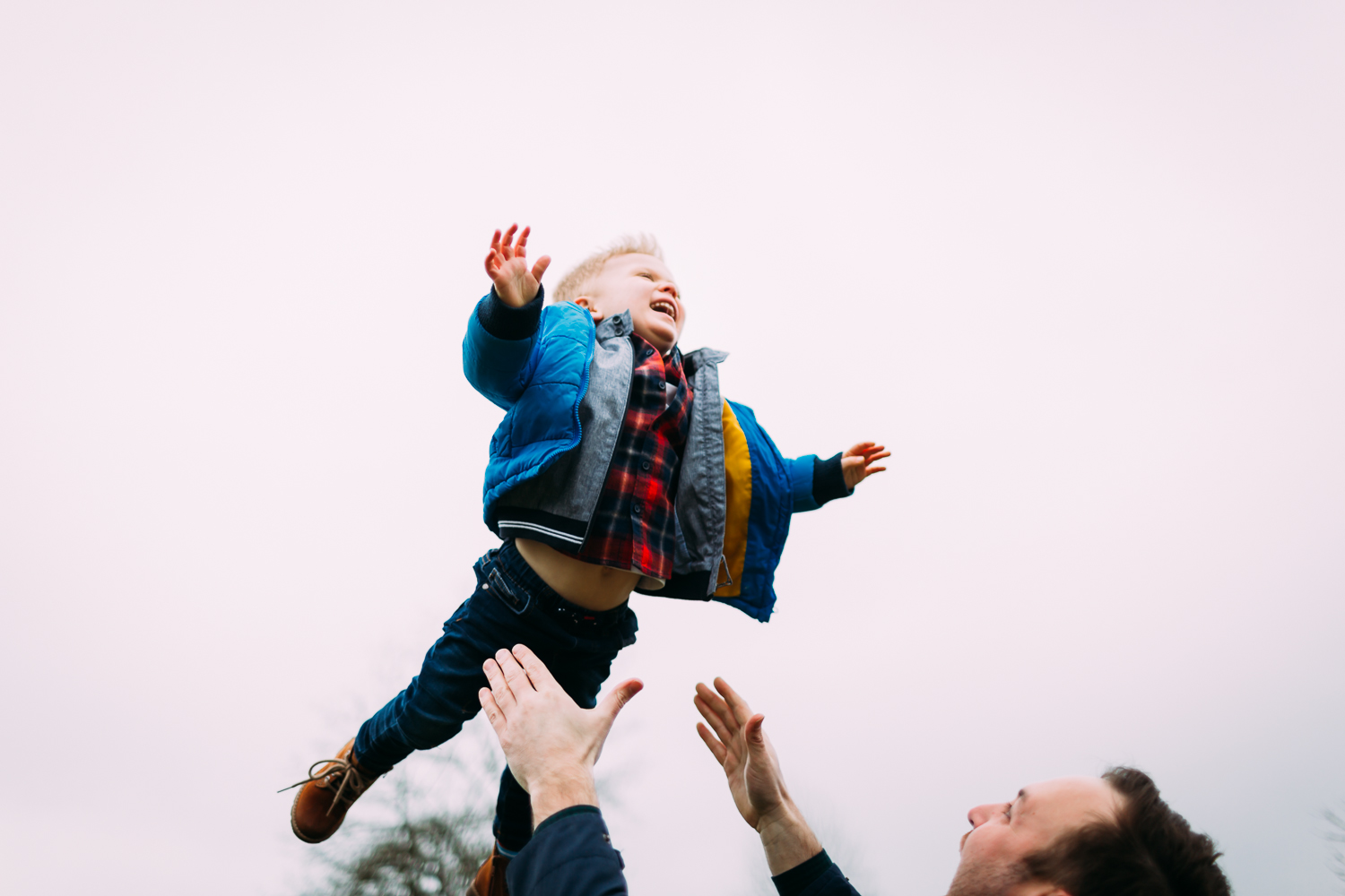 Father happily flinging his child in air and son laughing happily