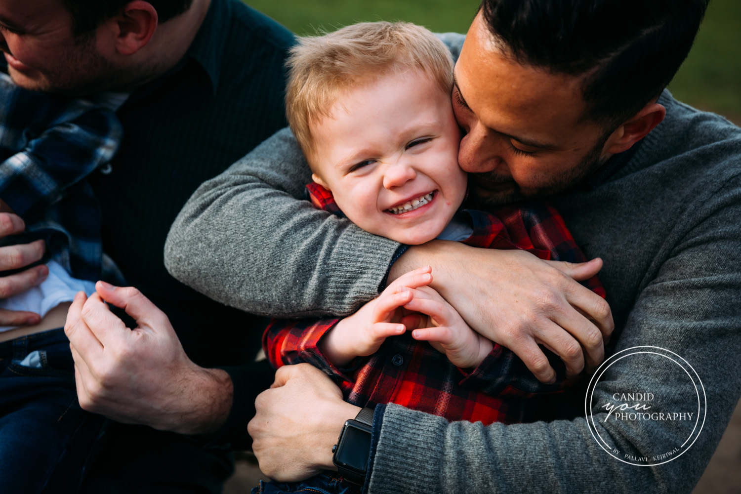 Dad tightly hugs laughing giggling son in park