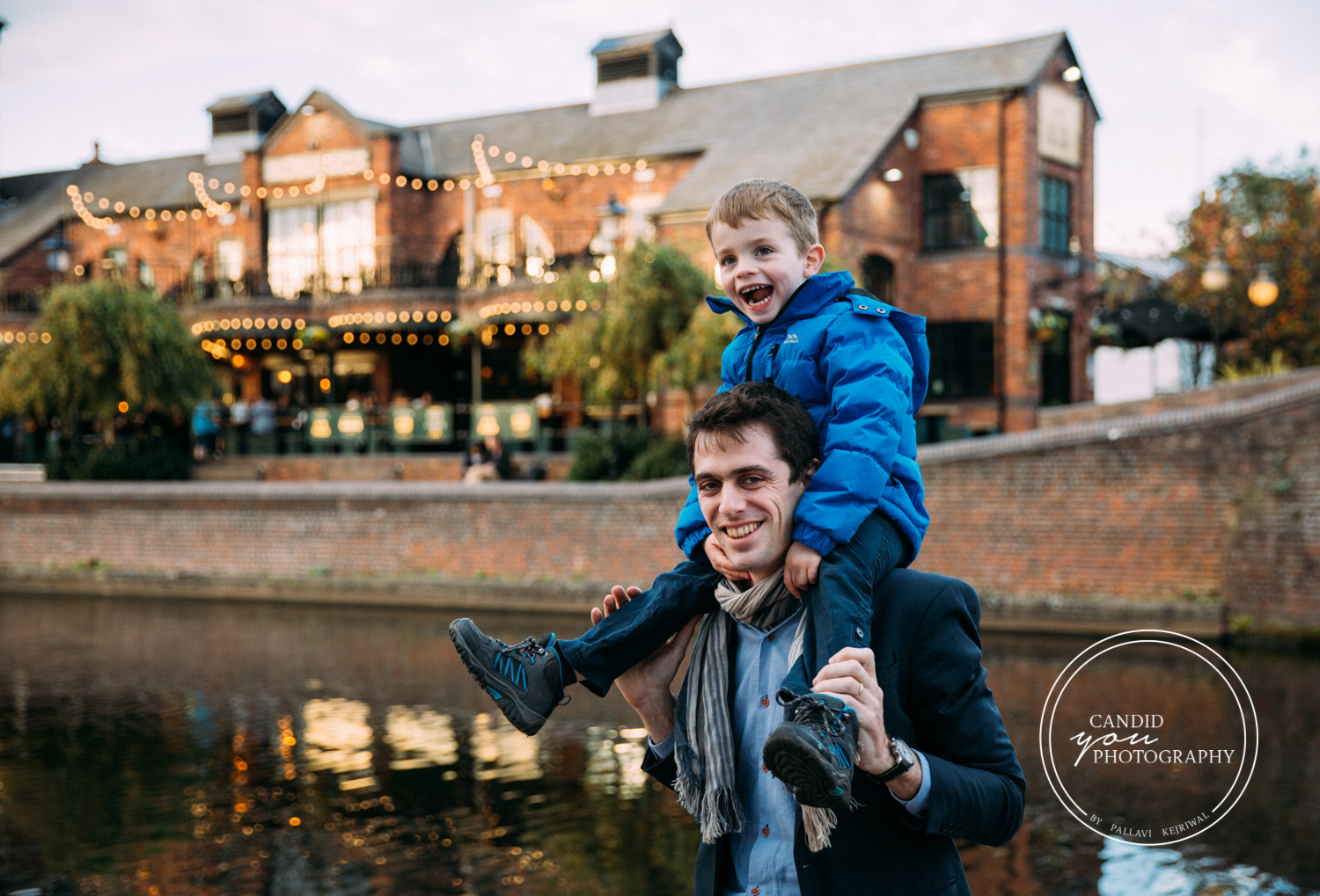 Boy sitting on Dad's shoulders next to Birmingham Canals in Brindley Place