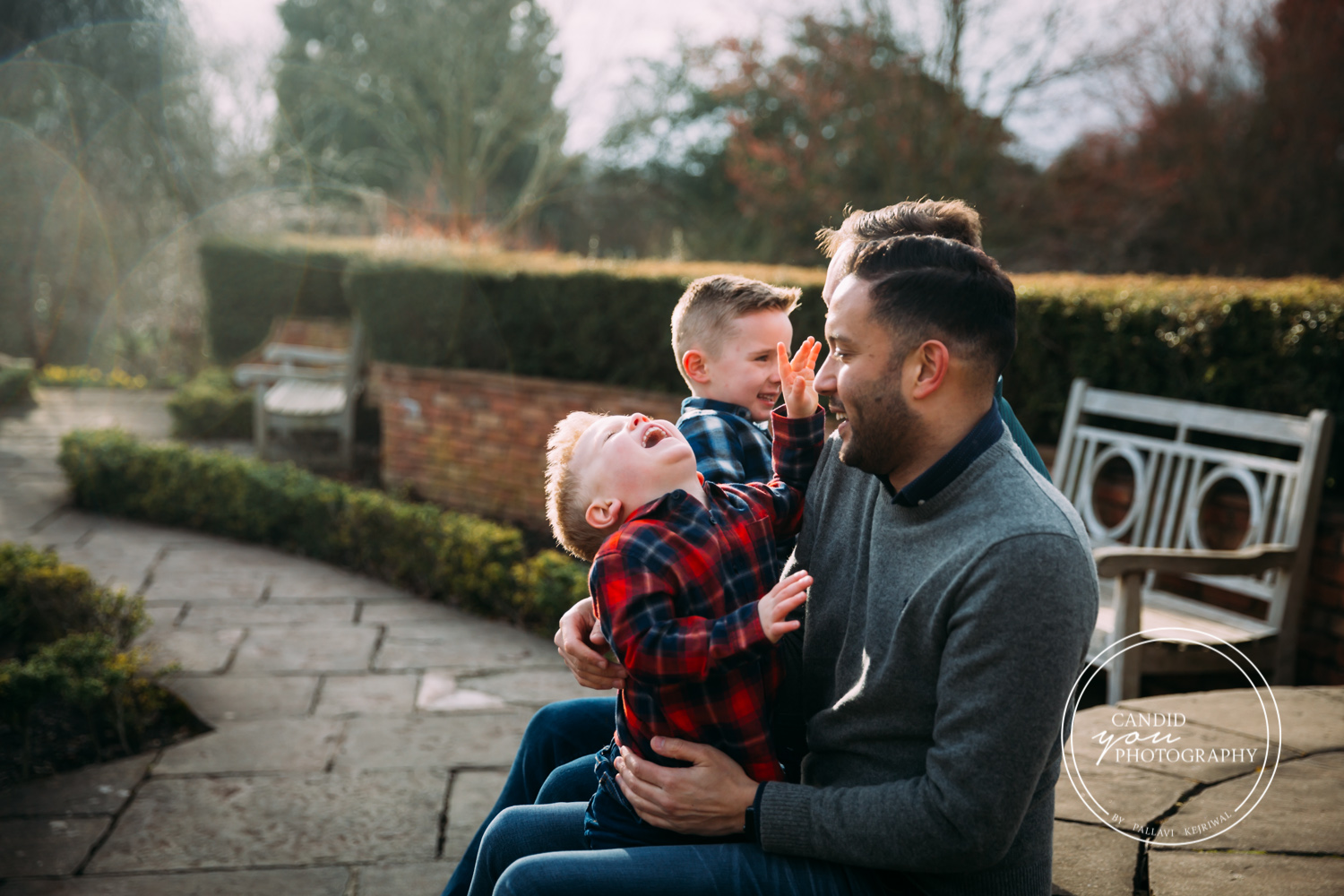 boys giggle uncontrollably while sitting on dad's laps and against setting sun