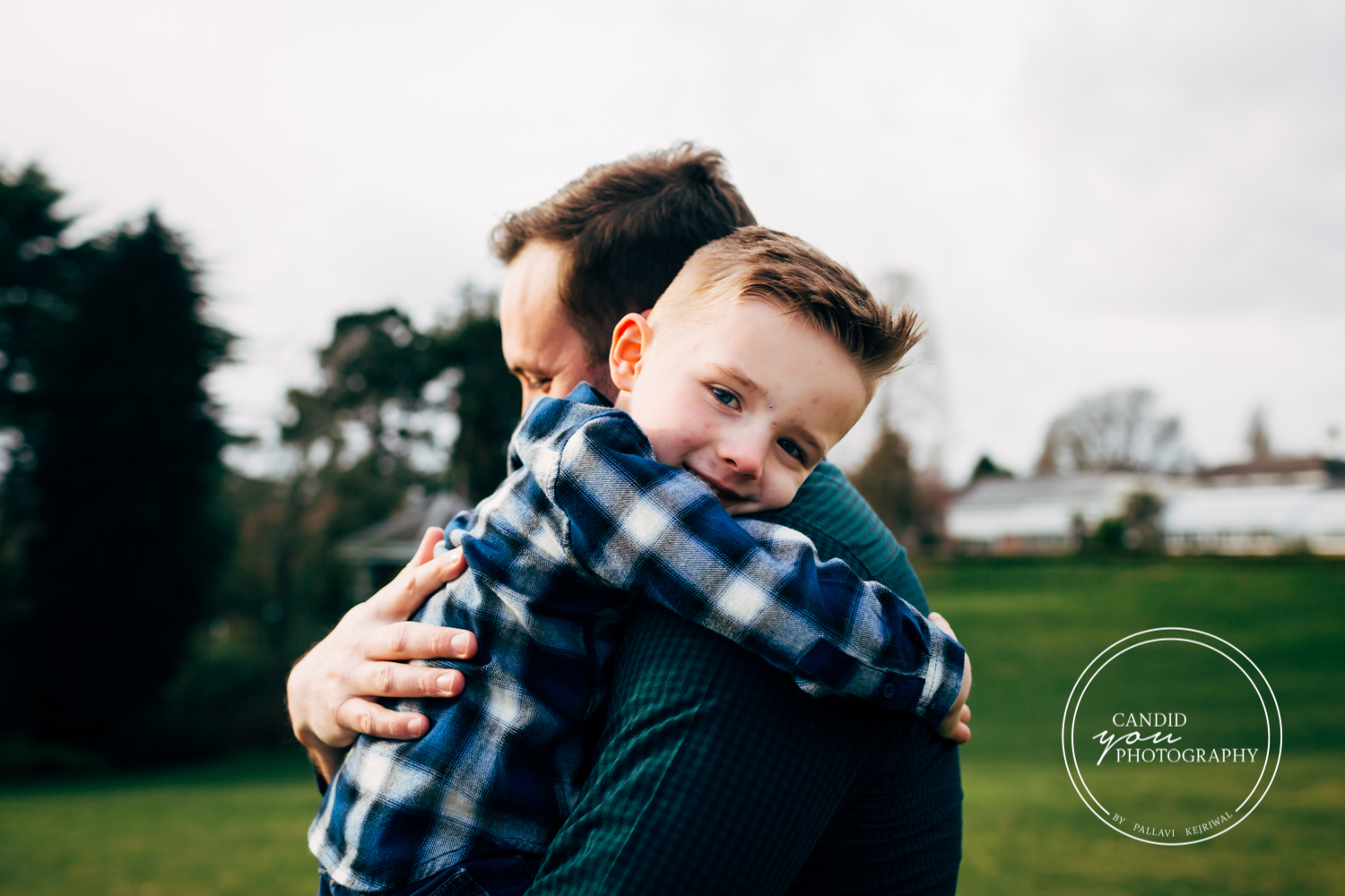 boy lovingly looks towards camera while being hugged by dad