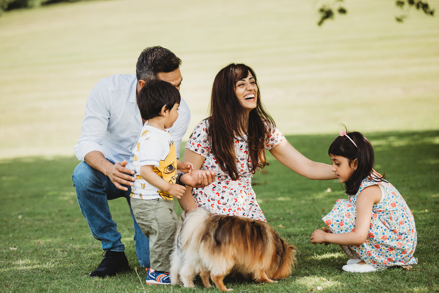 Family of four smiling in the park with dog