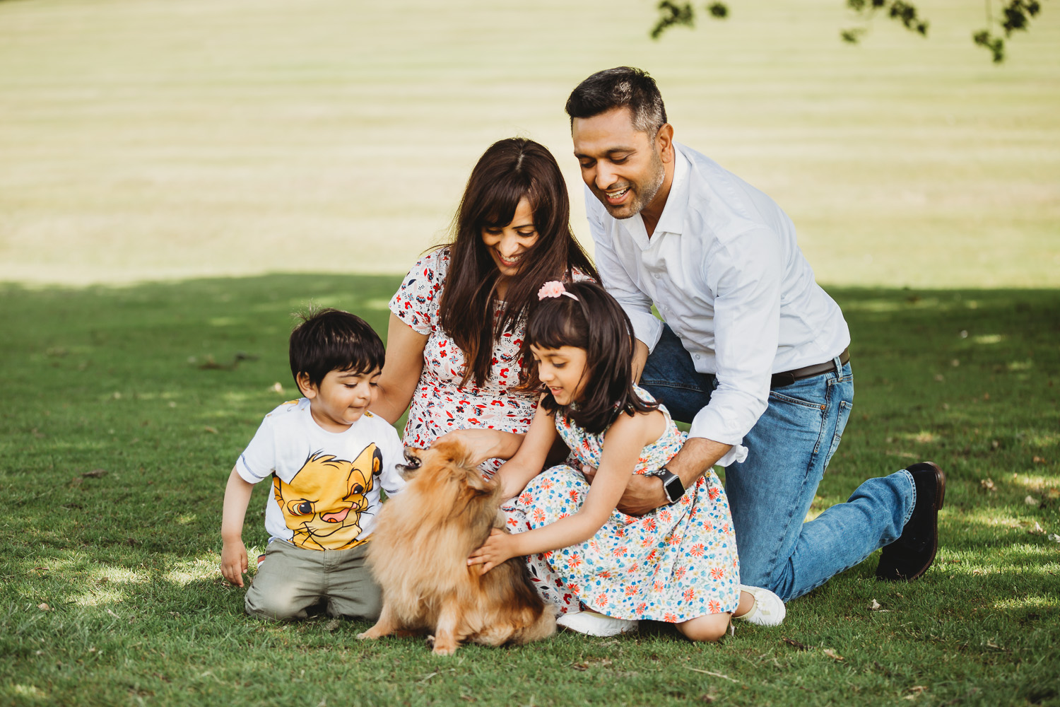 family of four enjoying with dog in park