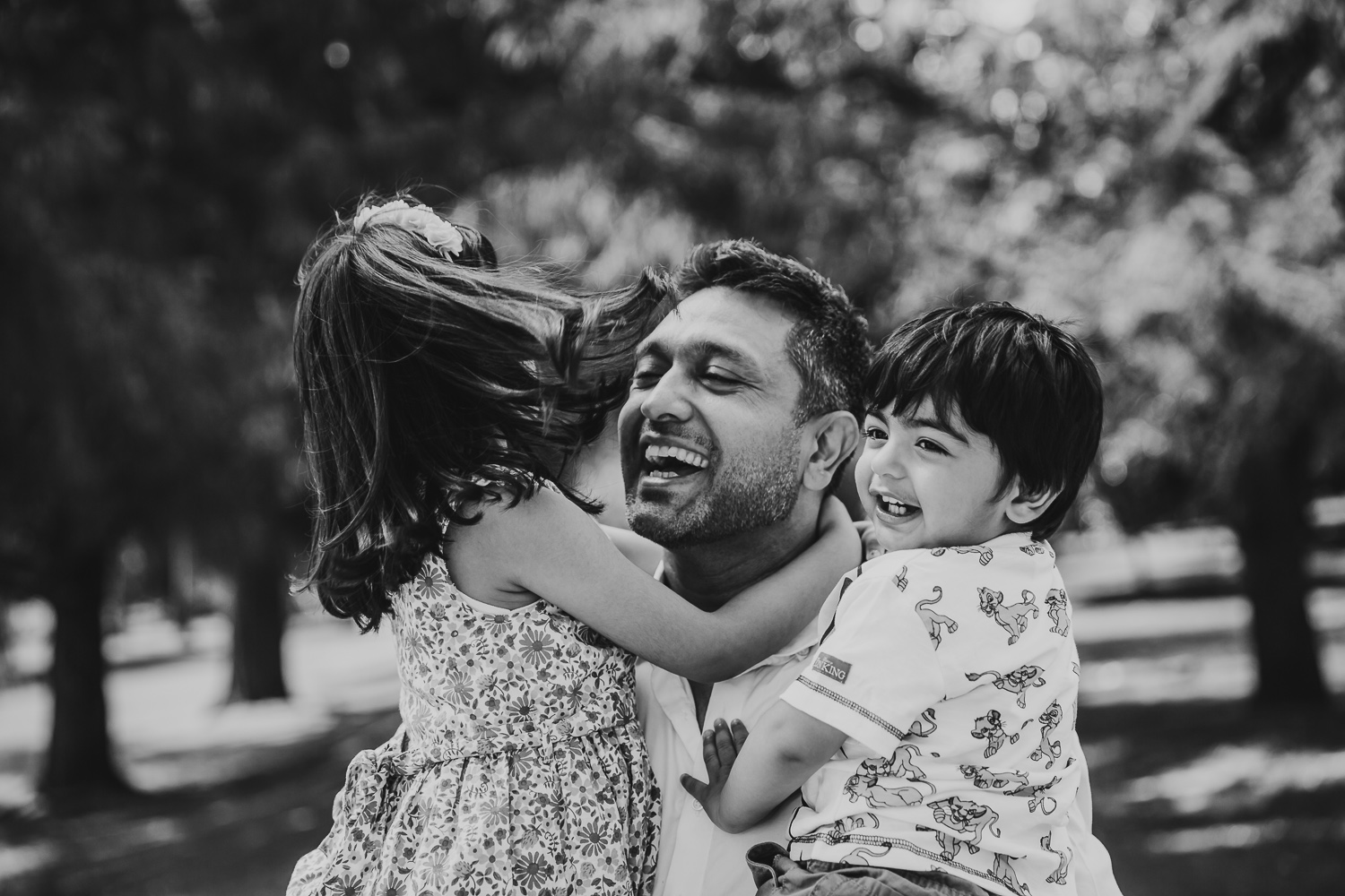 father laughs with and hugs his two children - one boy one girl