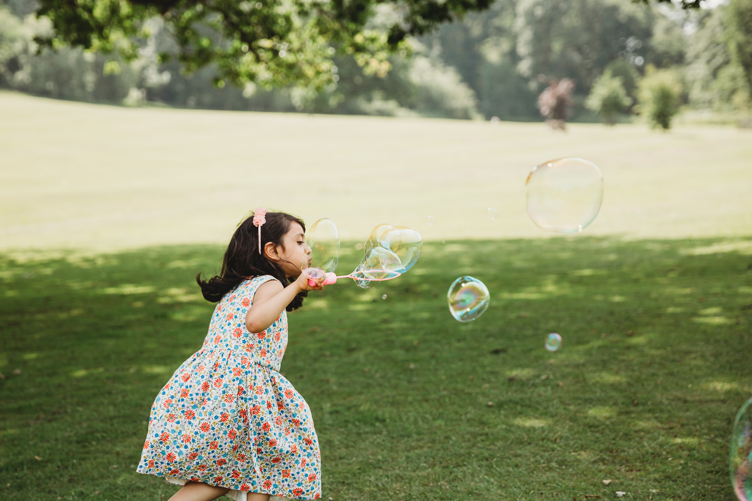Girl of four blows bubbles in the park
