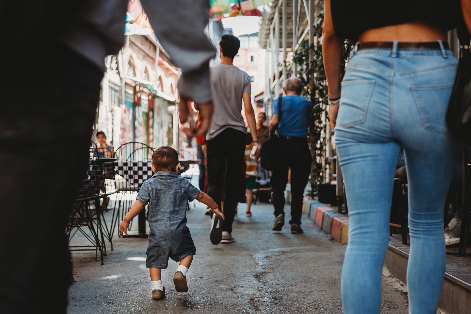 one year old walking on his own in a busy street
