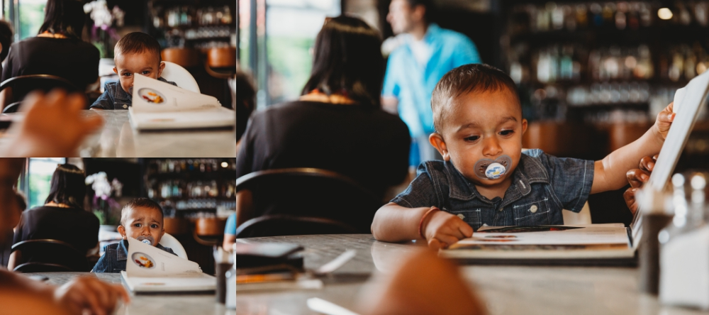 one year old boy looking through menu in cafe