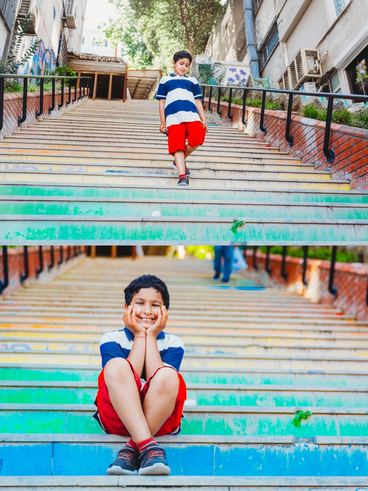 7 year old boy sitting on colourful steps and smiling