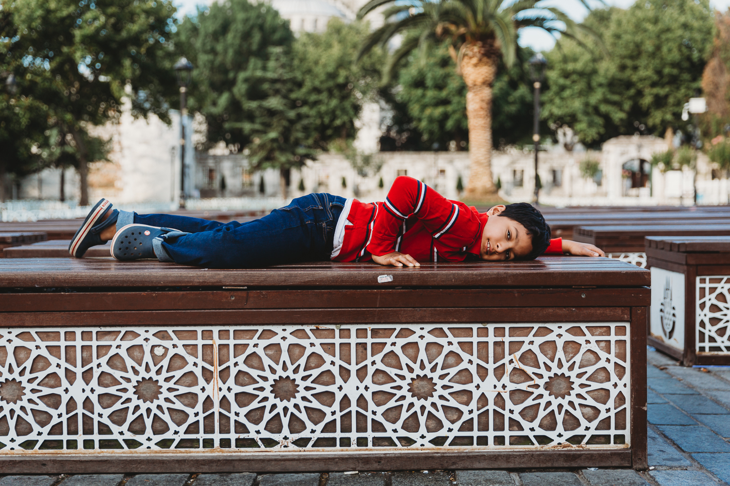 boy lying down on beautiful bench