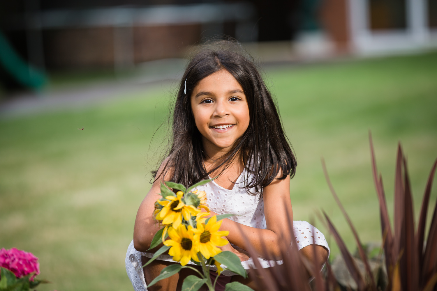 5 year old girl enjoying in her garden during in home family photo session
