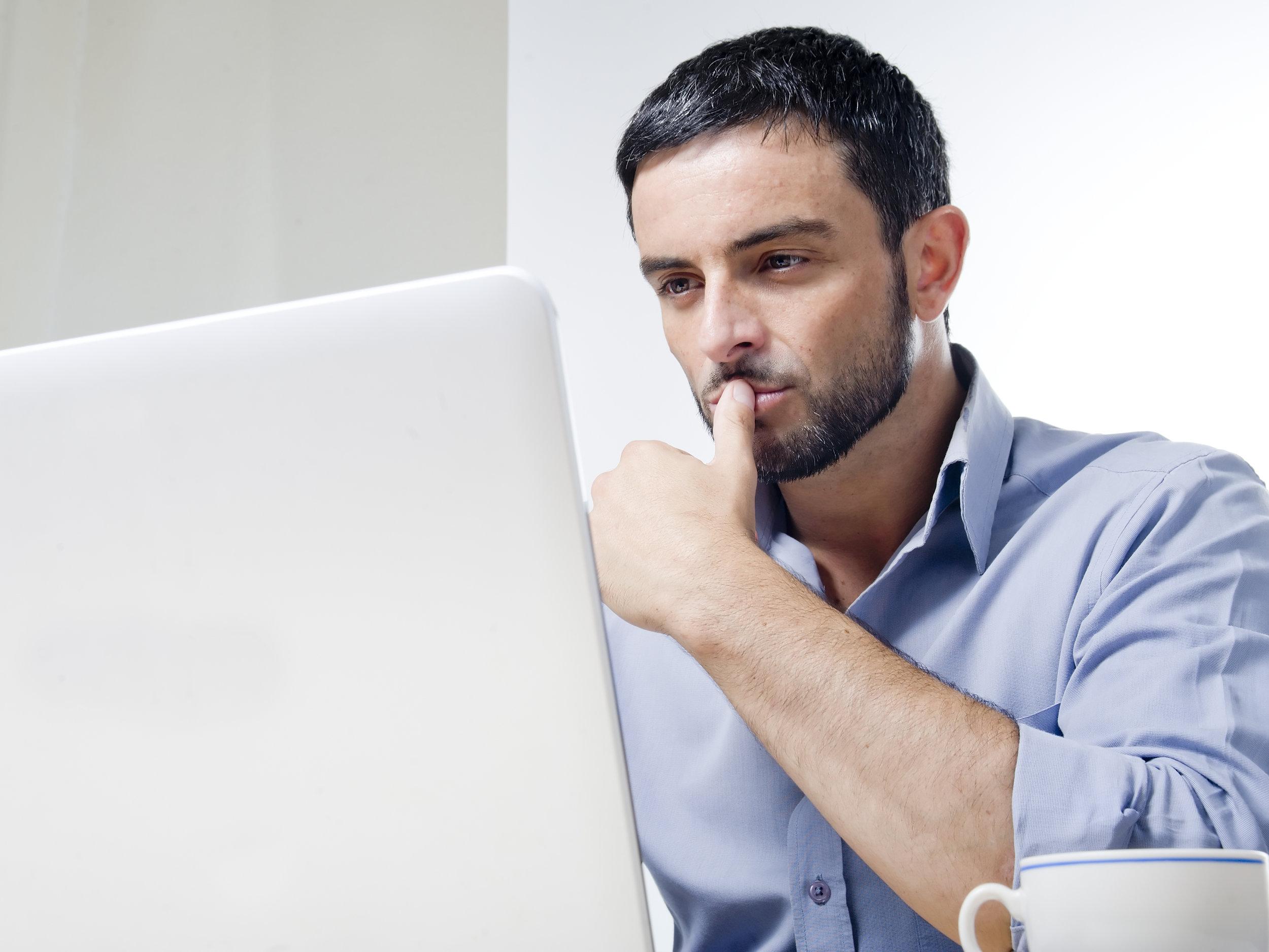 Young Man with Beard working on Laptop by OcusFocus  TRADUÇÃO E REVISÃO DE TEXTO