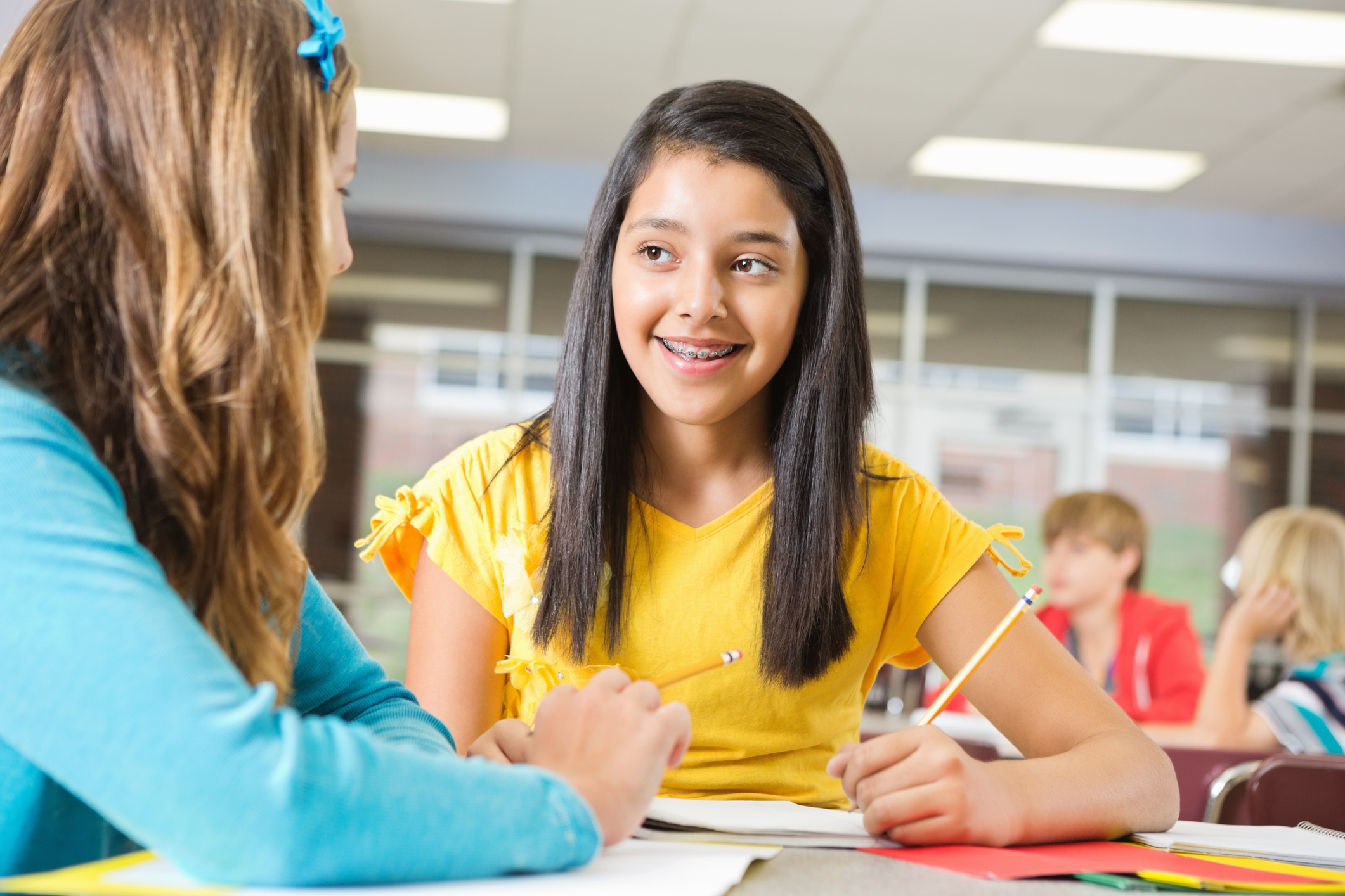Middle school girl studying with friend in class