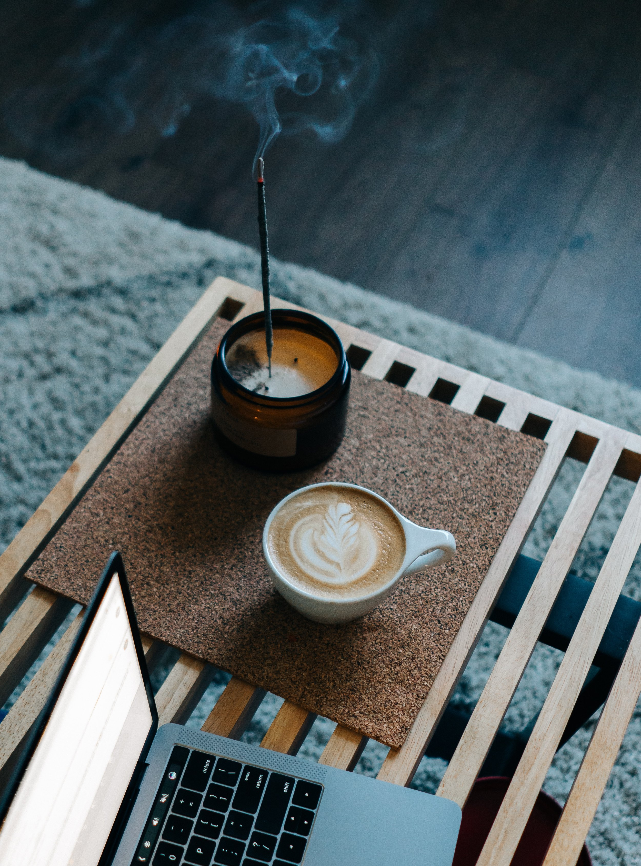 A cup of freshly-brewed coffee and slowly-burning incense pulls scents of nature into this workspace / Image Source:    Mike Marquez via Unsplash