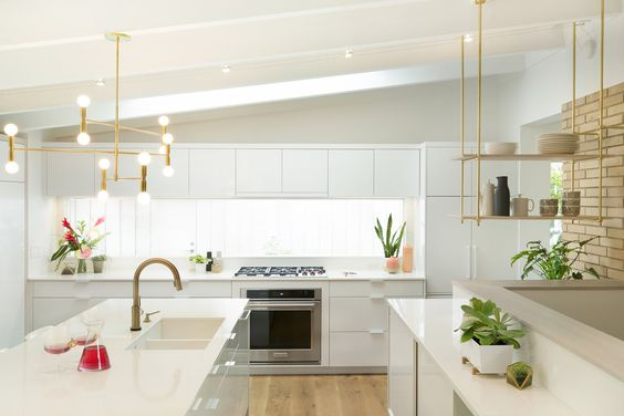 In our Midcentury Revitalization design, we used floating shelves suspended from the ceiling and brick wall by warm brass rods to create a visually open focal point. The brass also helps to connect with other warm metallic tones throughout the kitchen. / Design by    Vela Creative