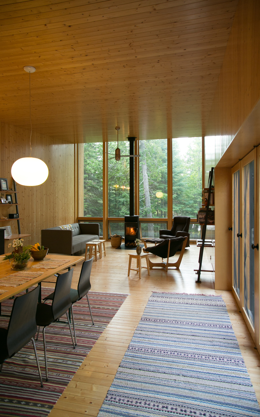 Curl up next to the modern fireplace for unbeatable lofted views of the forest and lakefront. /  Source