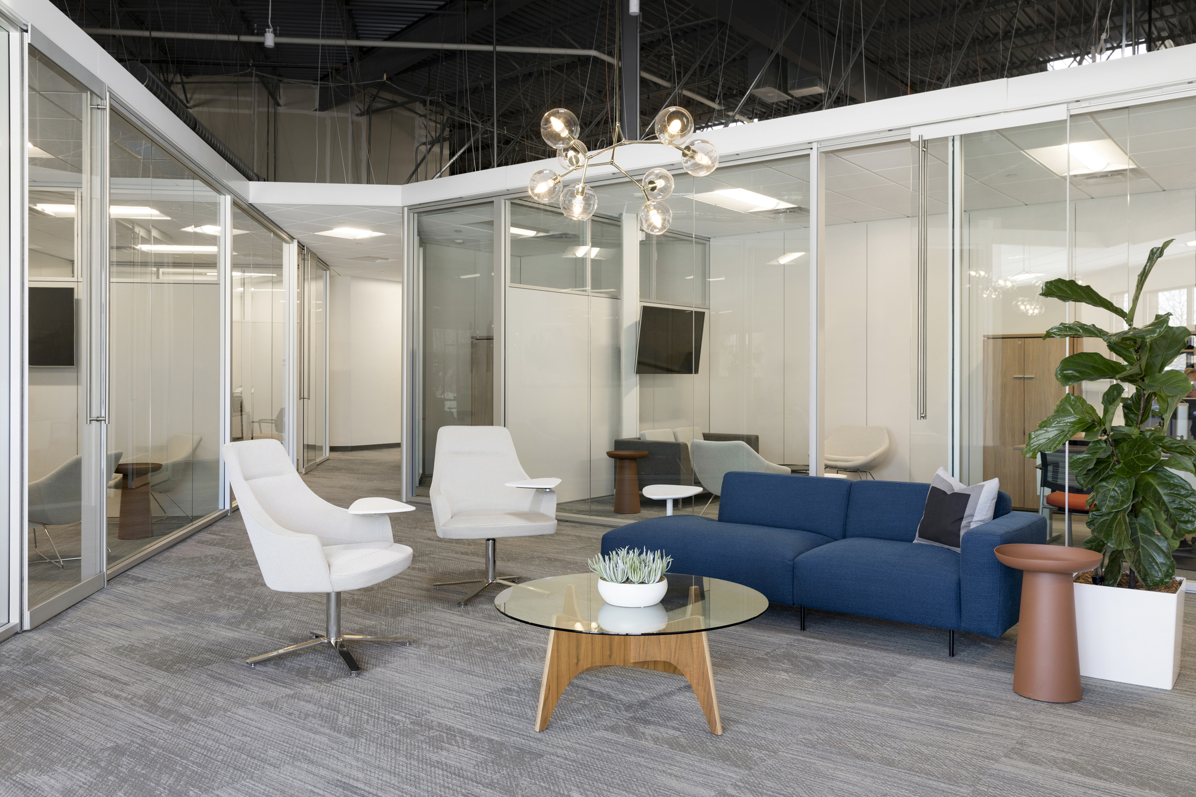 Surrounded by glass-enclosed offices and work areas, this shared lounge seating area provides space for collaboration while still feeling connected to the rest of the employees. / Design by Vela Creative