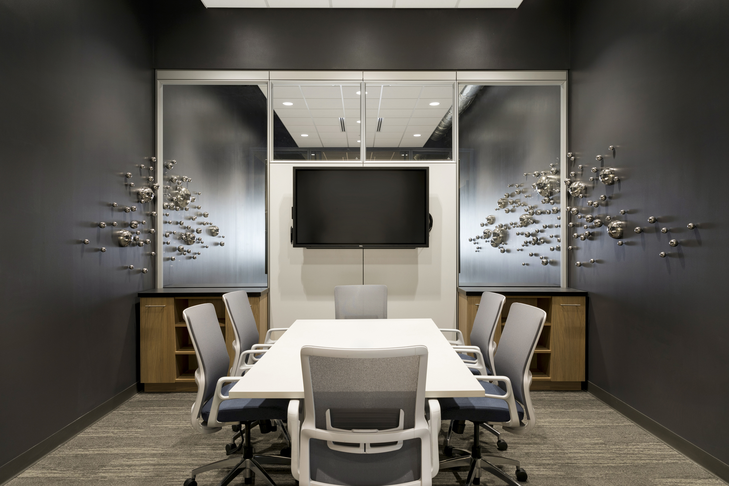 This conference room provides ample space for collaboration, while the sculptural wall art keeps the room in a perpetual state of visual interest and movement. / Design by    Vela Creative