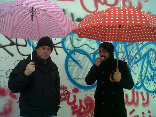 Peter and J in front of the Berlin Wall with umbrellas. J is eating Strudel.