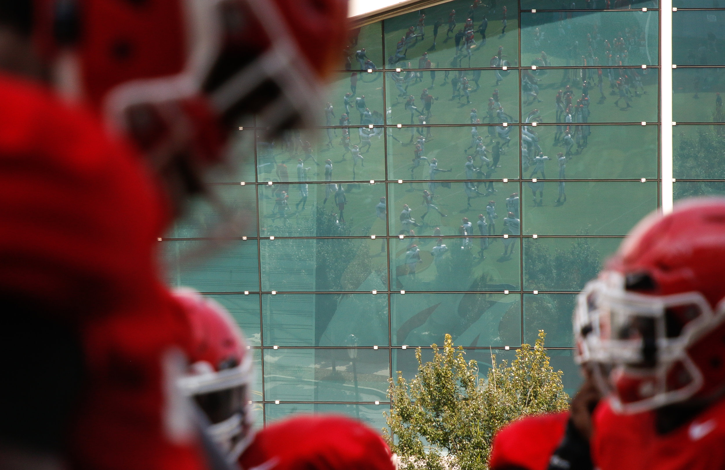 Georgia football preseason practice is reflected in the glass panels of Stegeman Coliseum in Athens, Ga., on Thursday, August 16, 2018.