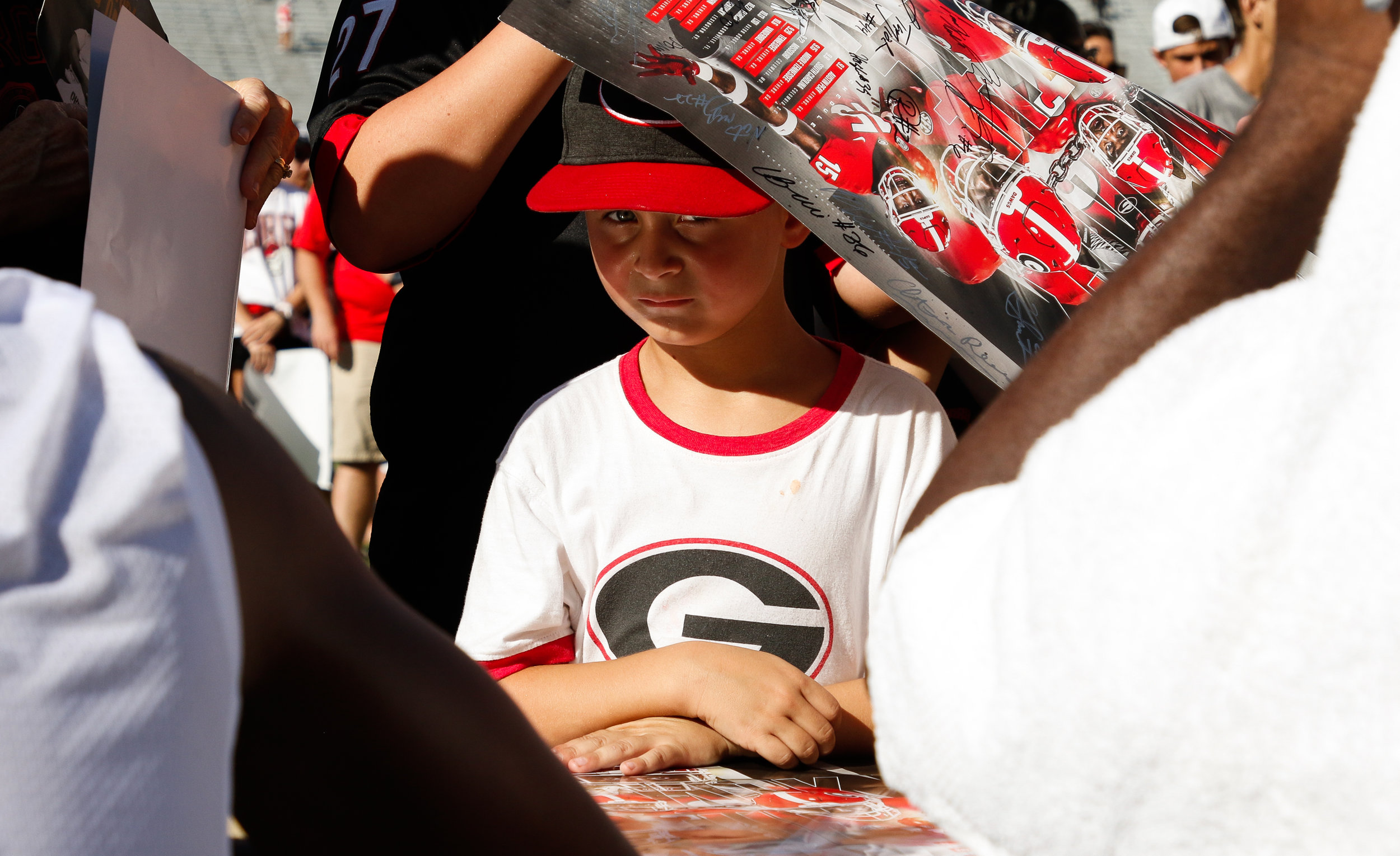 A young fan waits to have his poster signed by members of the Georgia football team on Fan Day in Sanford Stadium in Athens, Ga., on Saturday, Aug. 4, 2018.