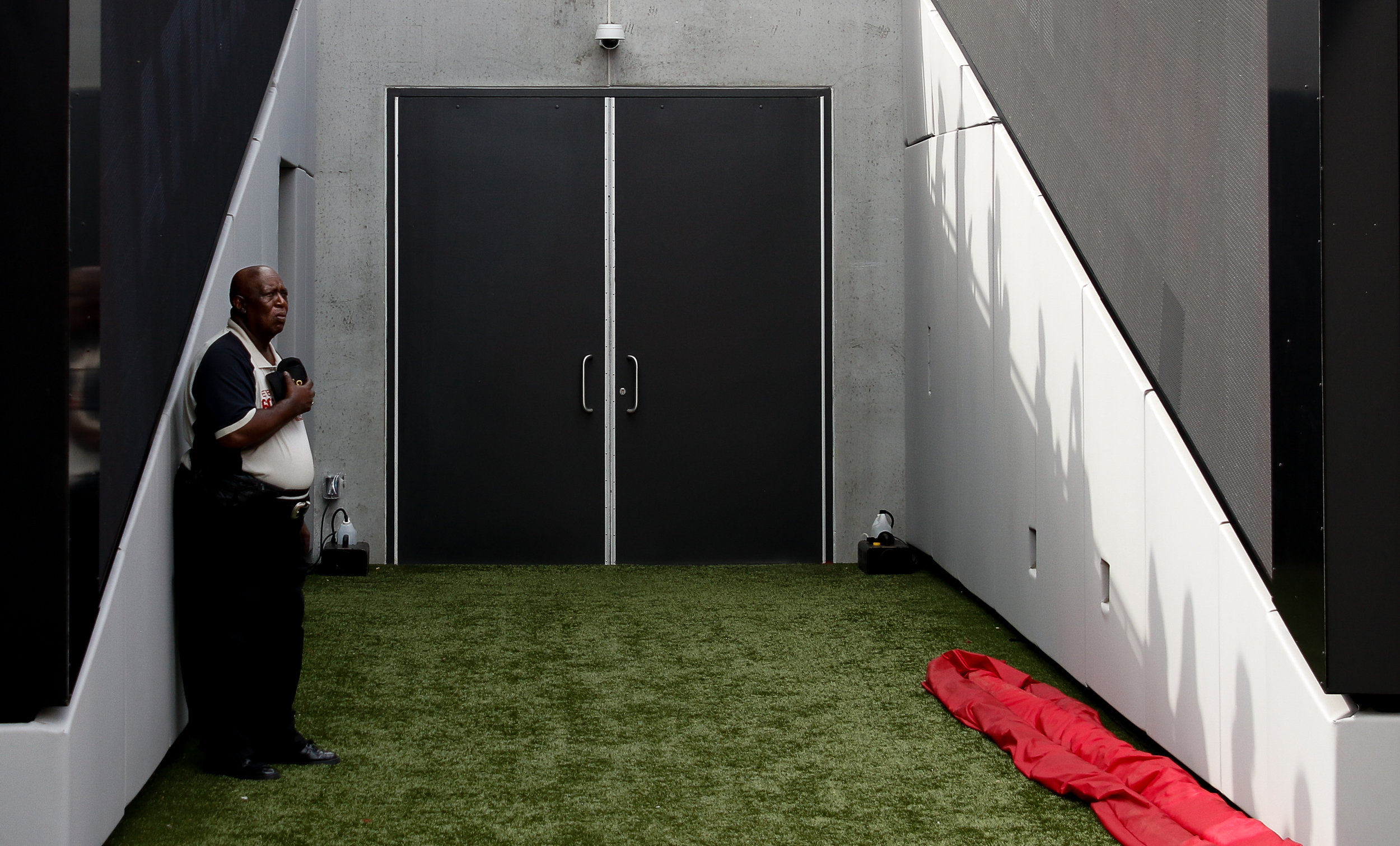 A member of the event staff stands outside of the Georgia Bulldogs' locker room during the National Anthem in Sanford Stadium on Saturday, September 29, 2018.