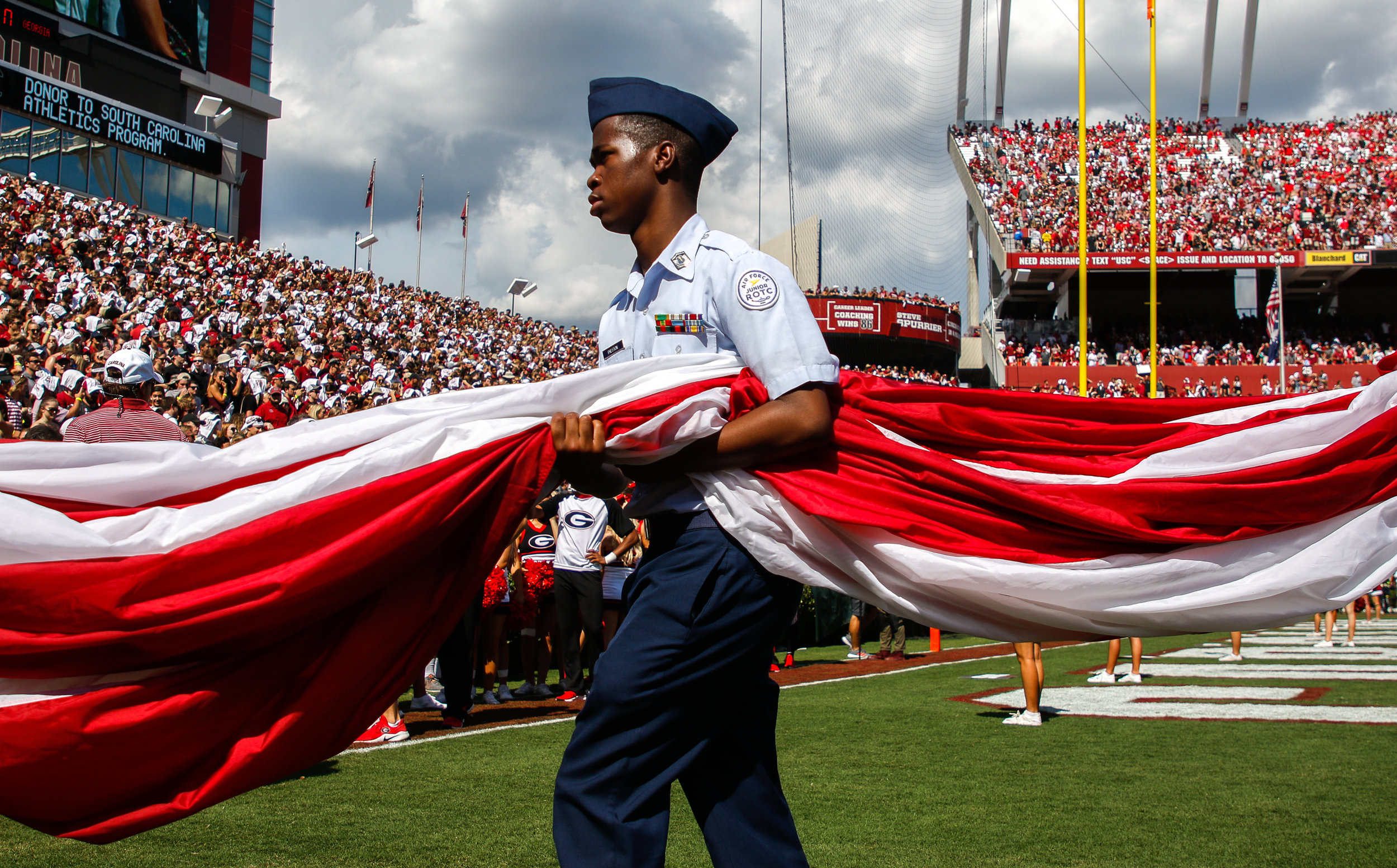 A junior Air Force ROTC member carries the American flag off the field following the singing of the National Anthem at a college football game between the University of Georgia and the University of South Carolina in Williams-Brice Stadium on Saturday, September, 8, 2018.