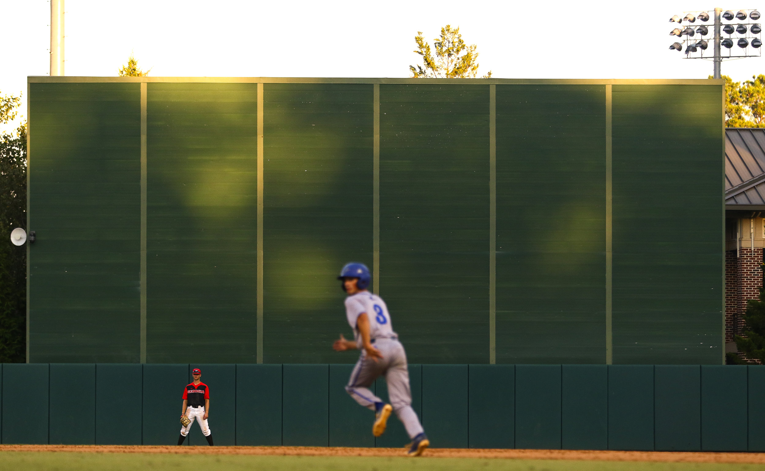 Gold light flickers on the Foley Field batter's eye screen as a UNC Asheville runner looks to take second during a baseball exhibition game between the University of Georgia and the University of North Carolina Asheville at Foley Field on Sunday, October, 14, 2018. (Photo by Kristin M. Bradshaw)