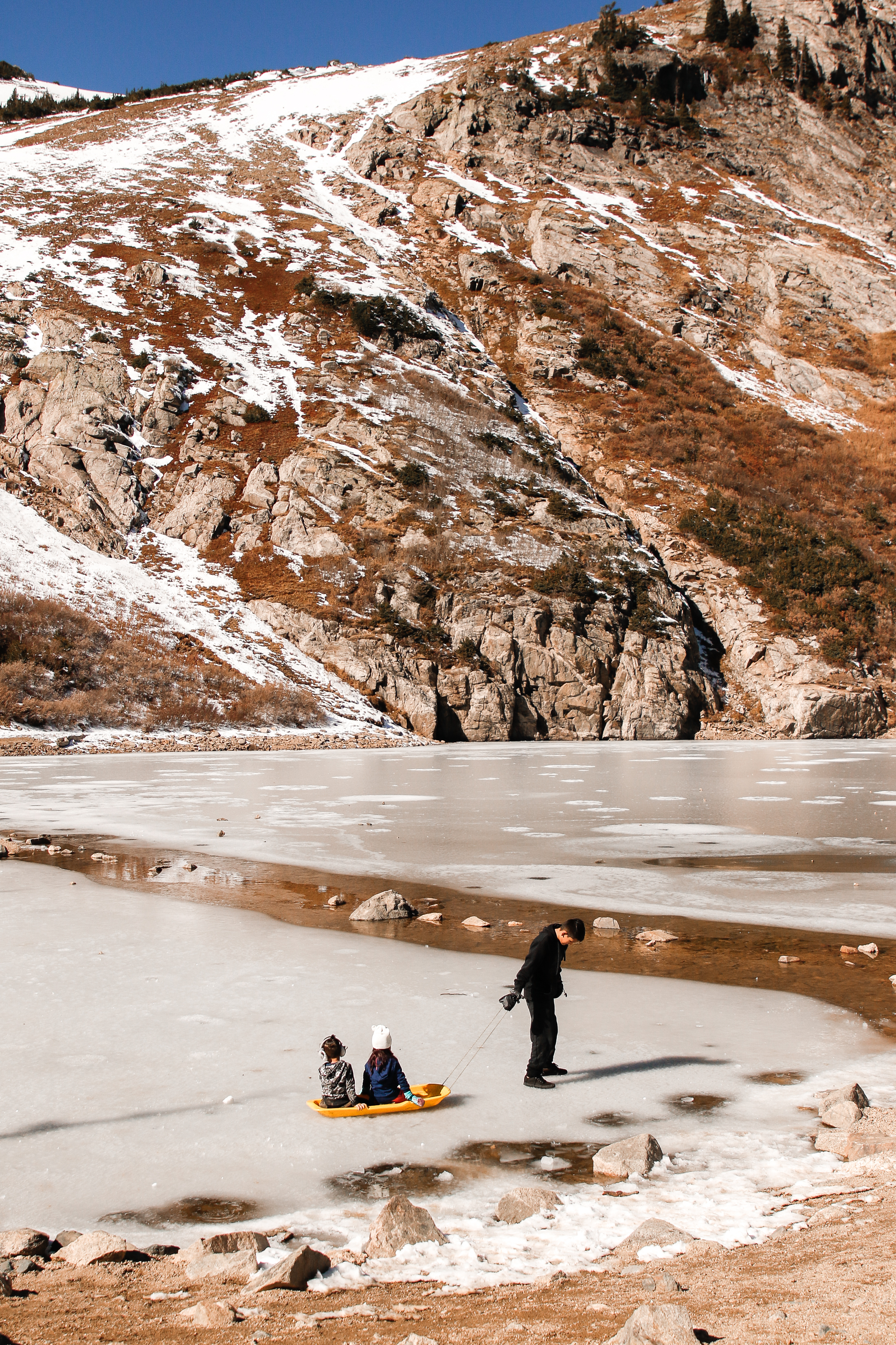 Two children enjoy a sled ride while another carefully pulls them across the frozen water at St. Mary's Glacier in Idaho Springs, Colorado, on Saturday, October 20, 2018.