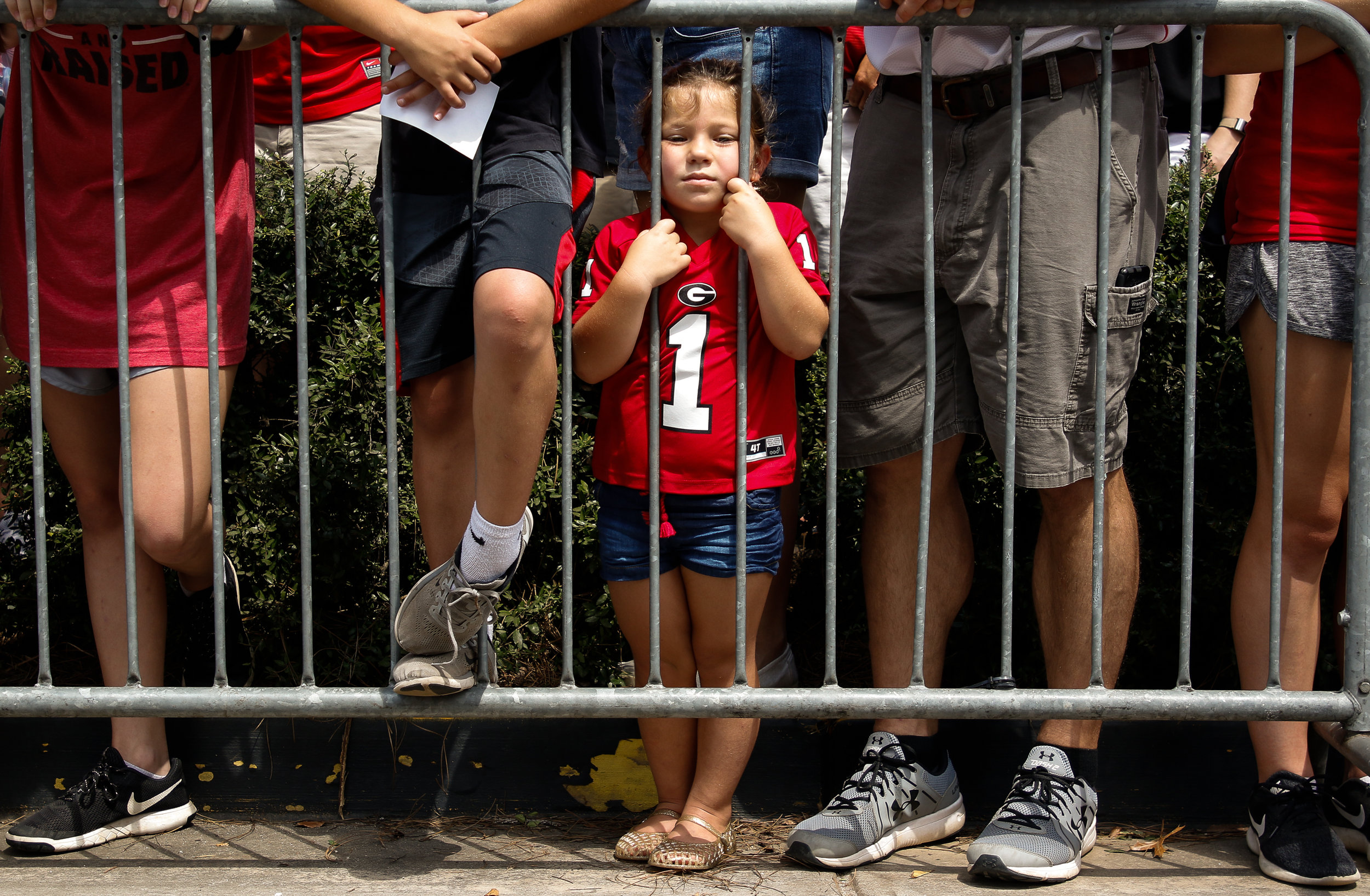 A young fan waits behind the barricade for the University of Georgia football team to arrive for their first Dawg Walk of the 2018 season in Athens, Georgia on Saturday, September 1, 2018.