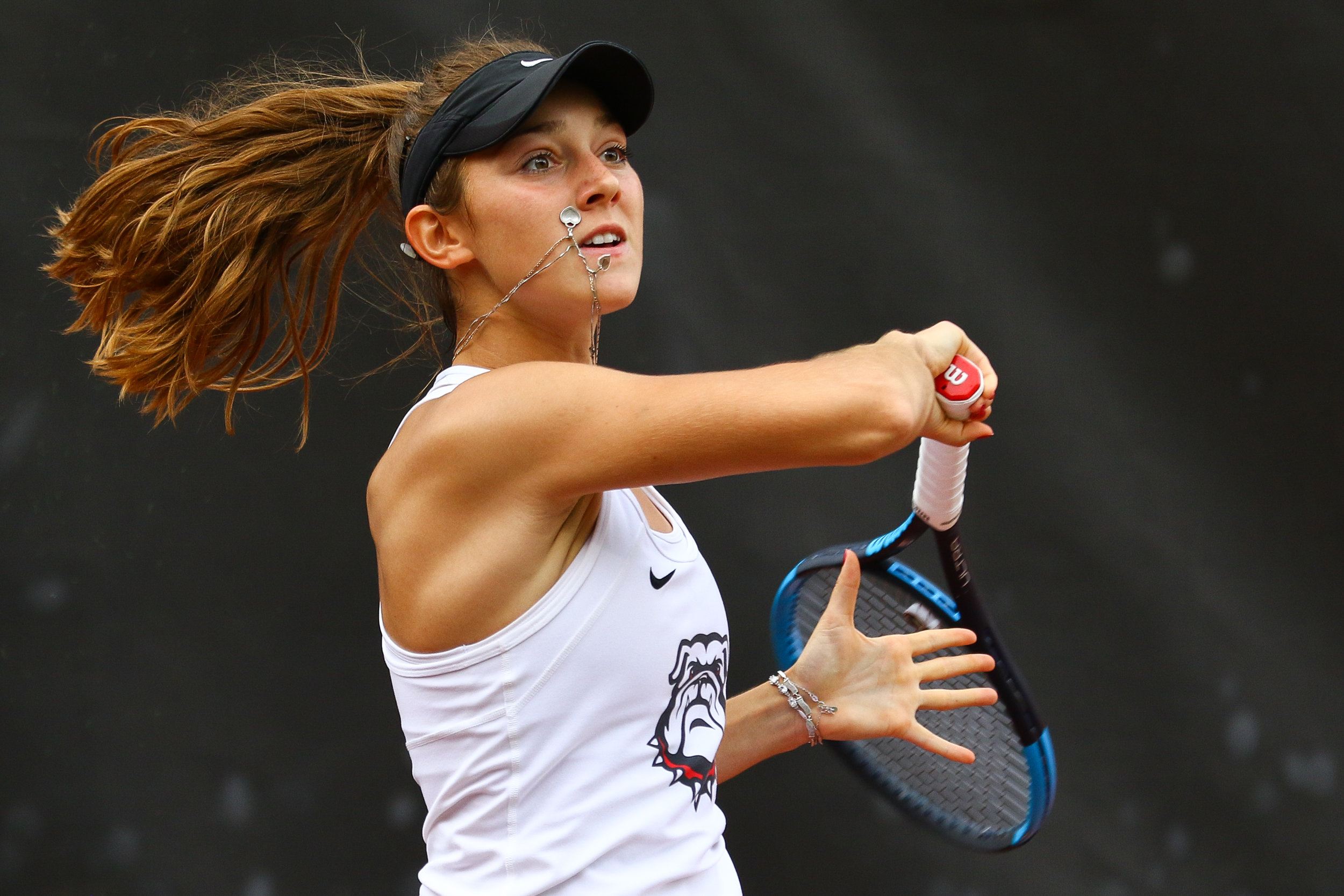Georgia's Katarina Jokic's necklace hits her cheek as she returns the ball during a singles match against Kentucky in Athens, Ga., on Friday, Apr. 12, 2019. Jokic's grandmother gifted her the chain, while her mother supplied the charmed heart. She wears it to every match.