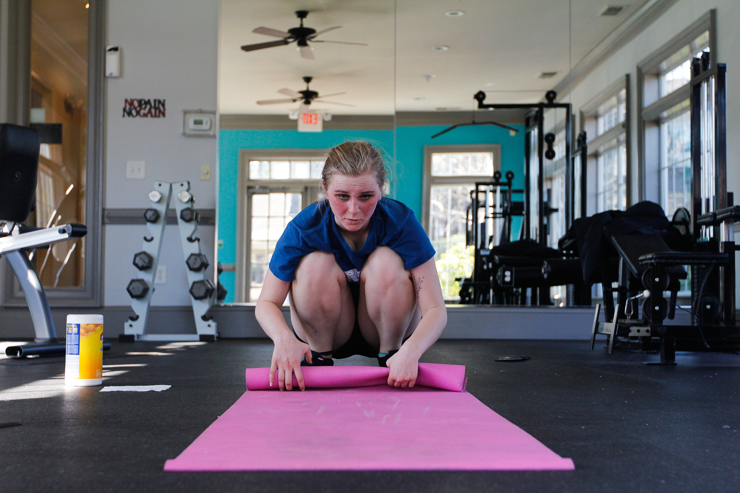 "Ashlynn Brown, 18, rolls up a yoga mat in the fitness center of her apartment complex in Woodstock, Ga., on Sunday, March 19, 2017. ""I love the idea of suffering. There's also a part of me that loves testing the limits of my body,"" says Ashlynn. Since entering recovery from her eating disorder, she searches for satisfaction through exercise. Her rigorous, two hour routine is her outlet."
