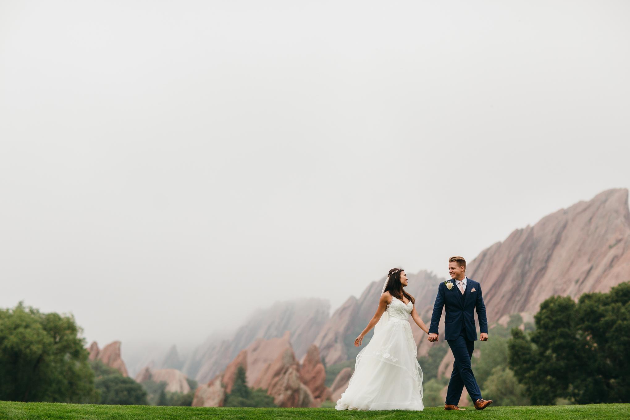 Couple walking hand in hand Arrowhead Golf, Red Rocks of Colorado