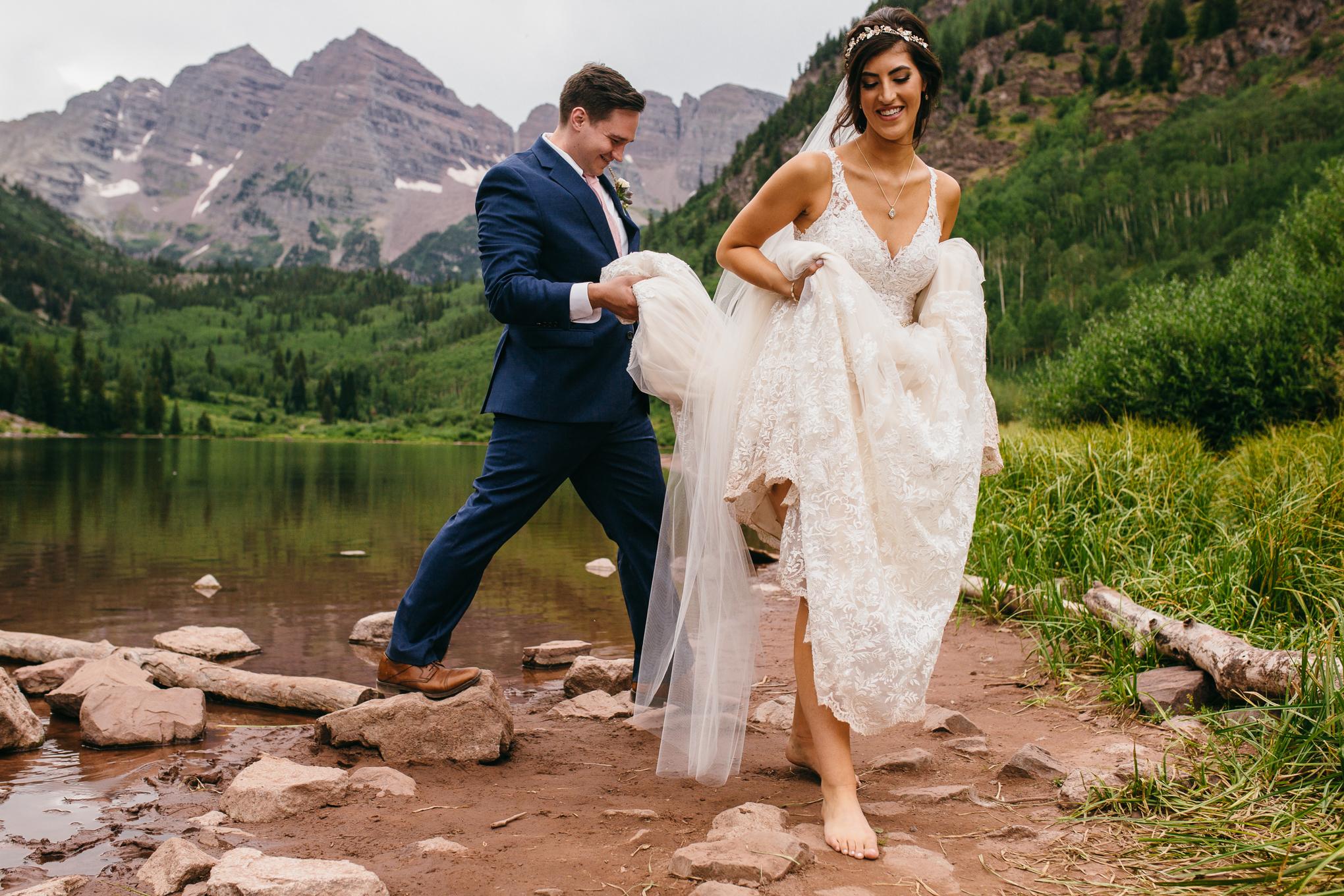 Smiling elopement couple walking away from Maroon Bells, Aspen Colorado.