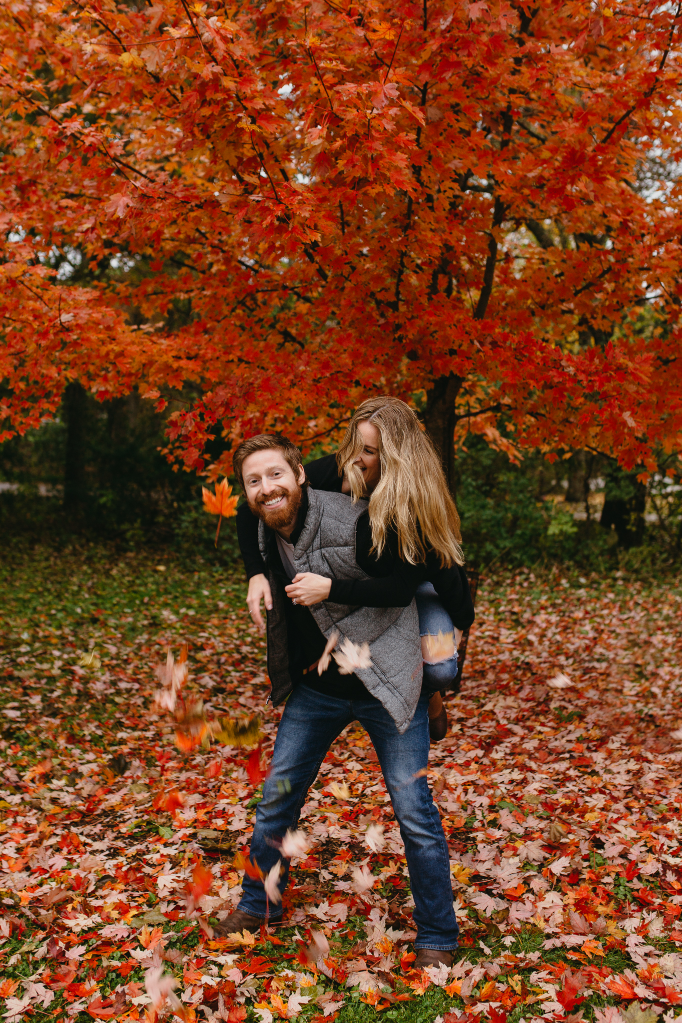 Engaged couple laughing and playing amidst bright red leaves in fall in Chicago.