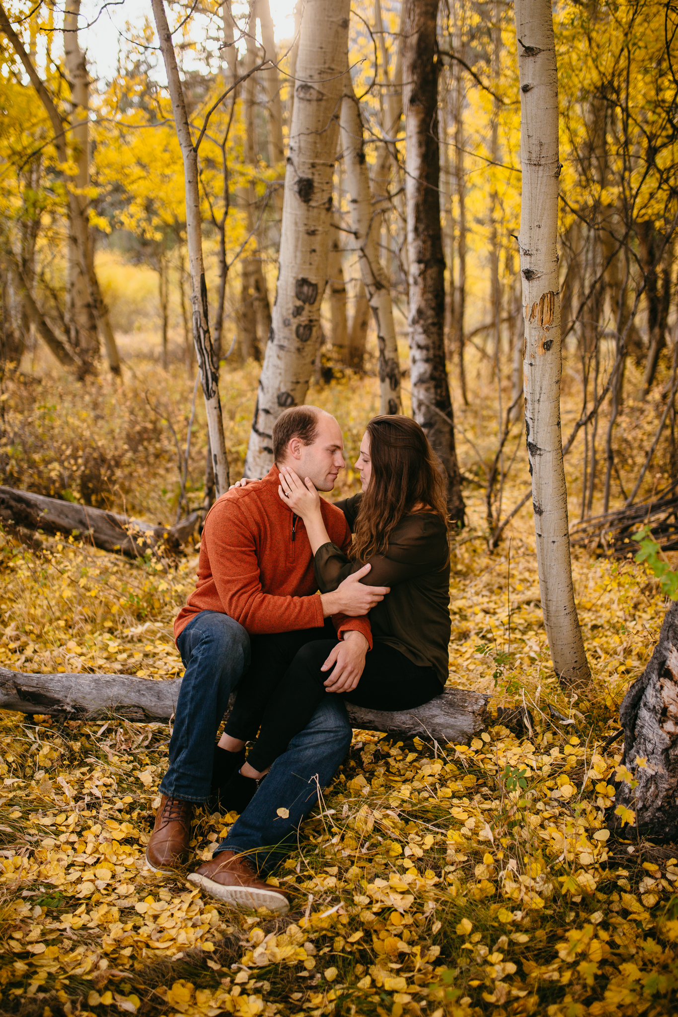 Engaged couple holding one another in beautiful yellow aspen grove in fall in Twin Lakes, Colorado.